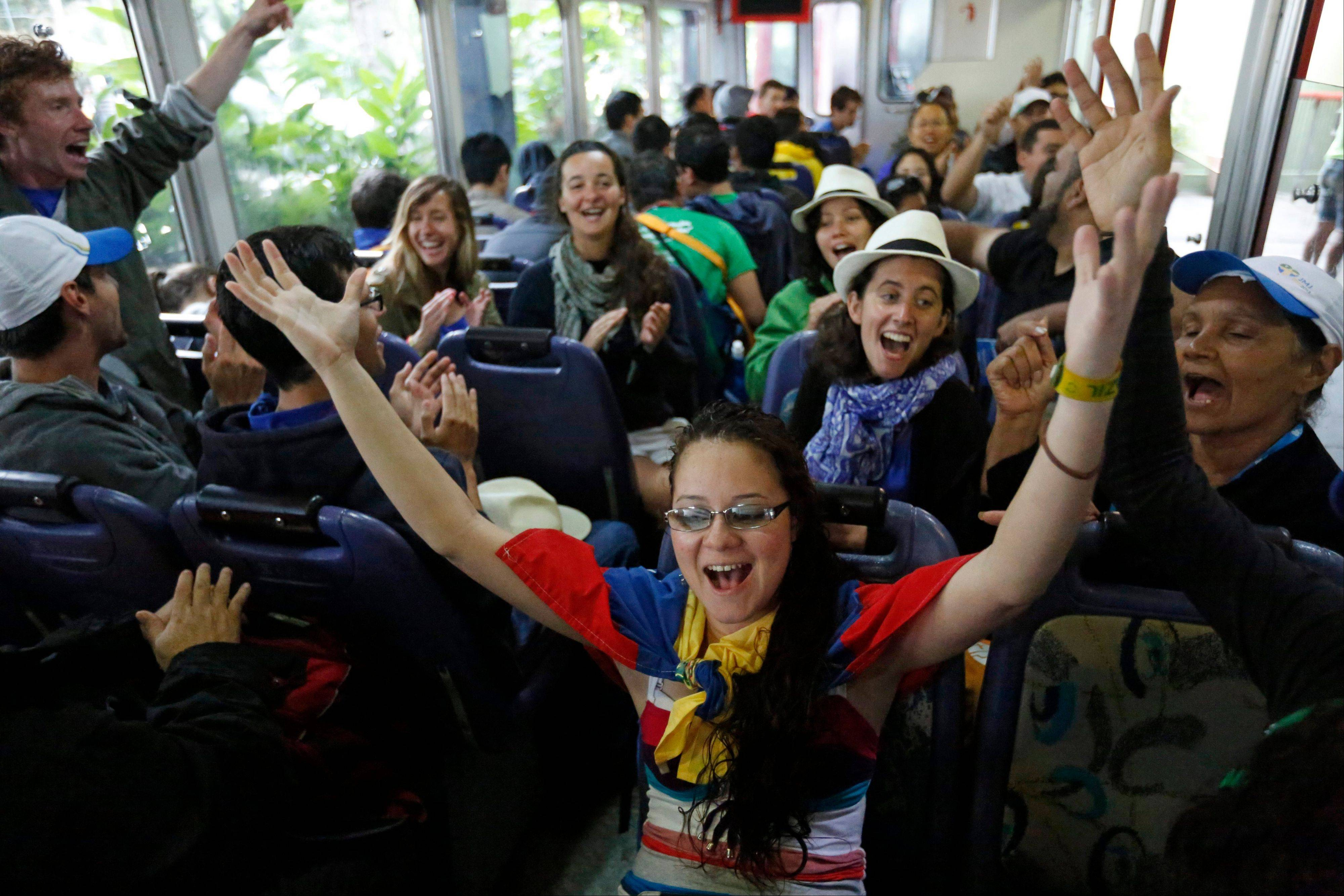 Youth from France, Venezuela and Canada who are in Brazil for World Youth Day events sing songs as they ride in a train that travels to Corcovado mountain where the statue Christ the Redeemer stands over Rio de Janeiro, Brazil, Tuesday, July 23, 2013. The pope is here on a seven-day visit meant to fan the fervor of the faithful around the globe.