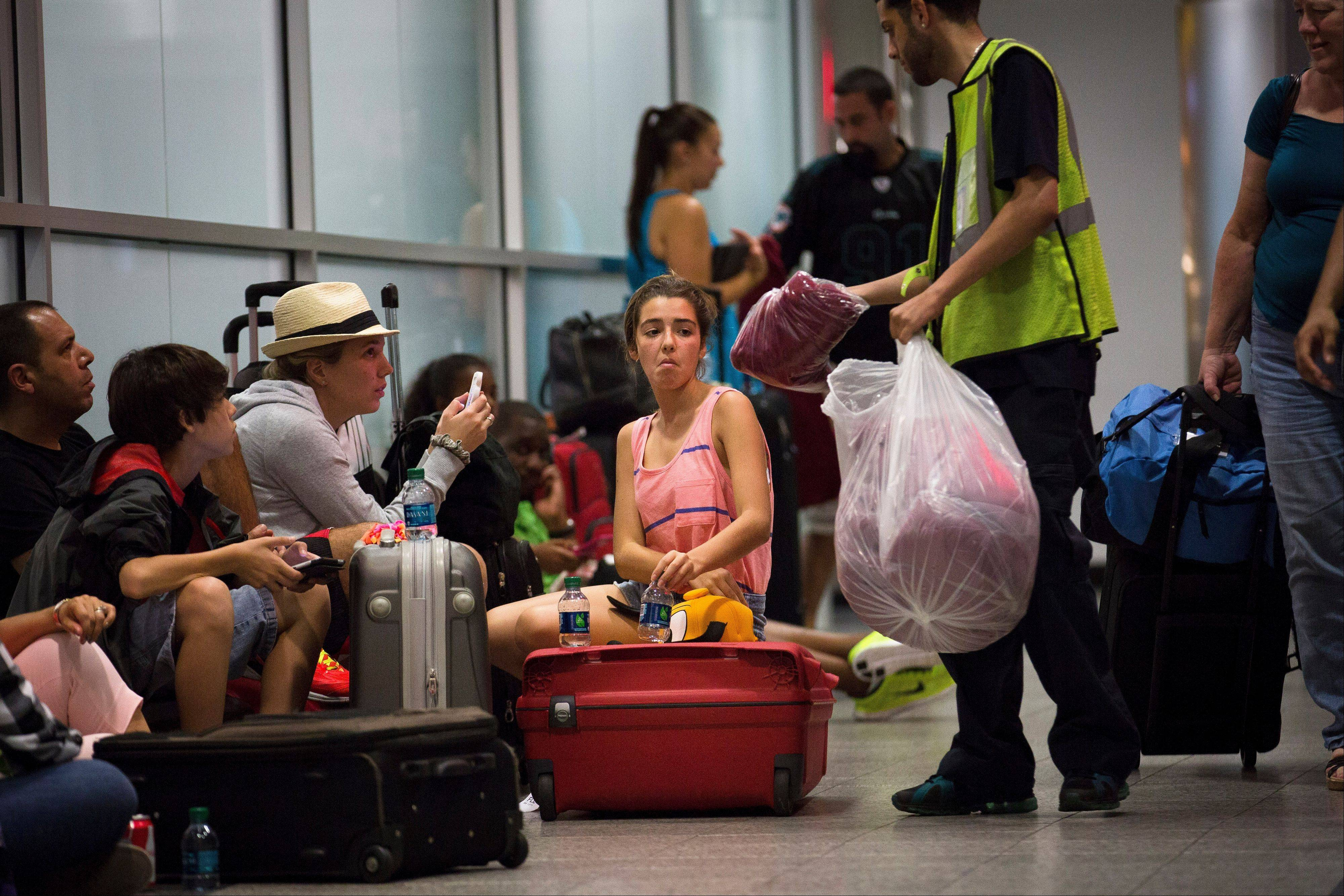 Stranded passengers are handed blankets while they wait at LaGuardia Airport as multiple flights were canceled after a Southwest Airlines 737 plane's nose gear collapsed during a landing, Monday, July 22, 2013, in New York. The airport fully reopened Tuesday
