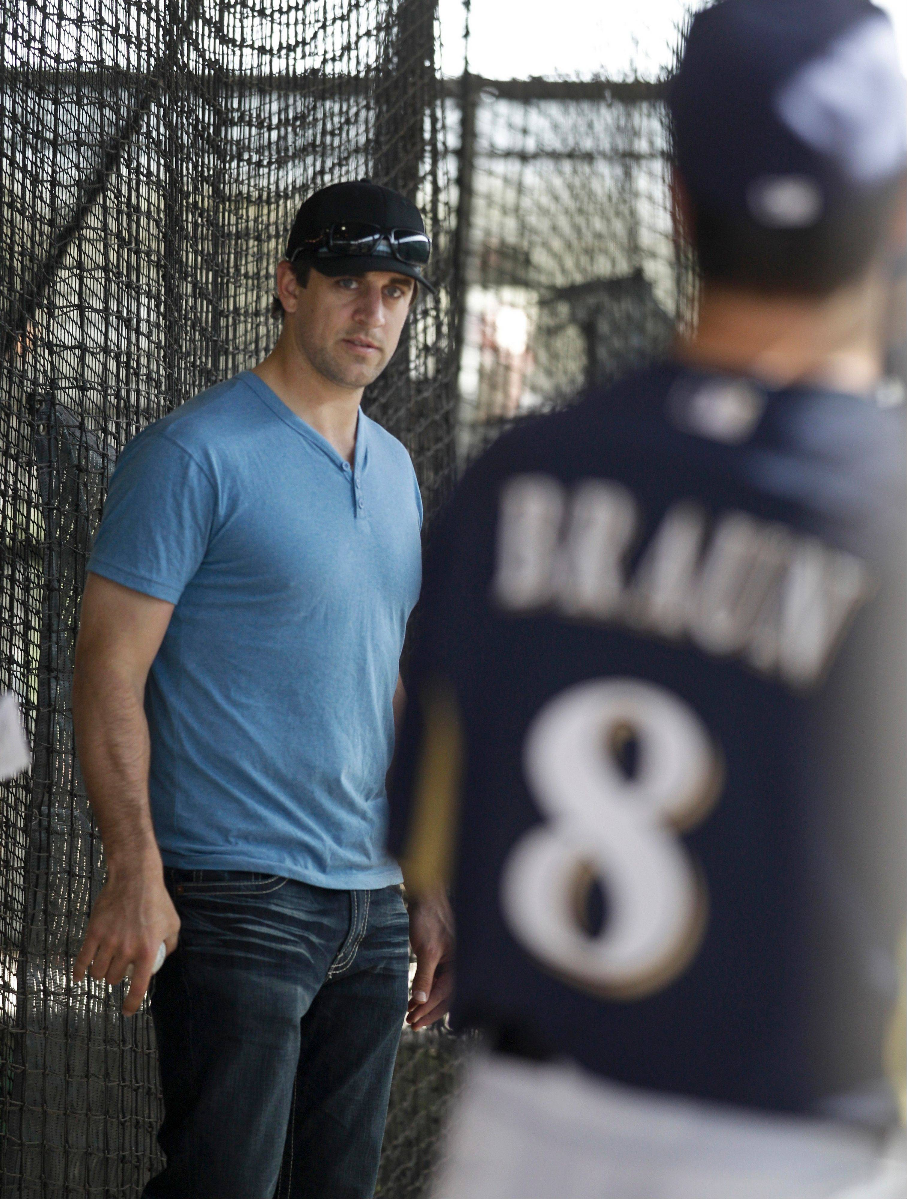 The Brewers' Ryan Braun, right, and Green Bay Packers quarterback Aaron Rodgers chat during a spring training workout in Phoenix.