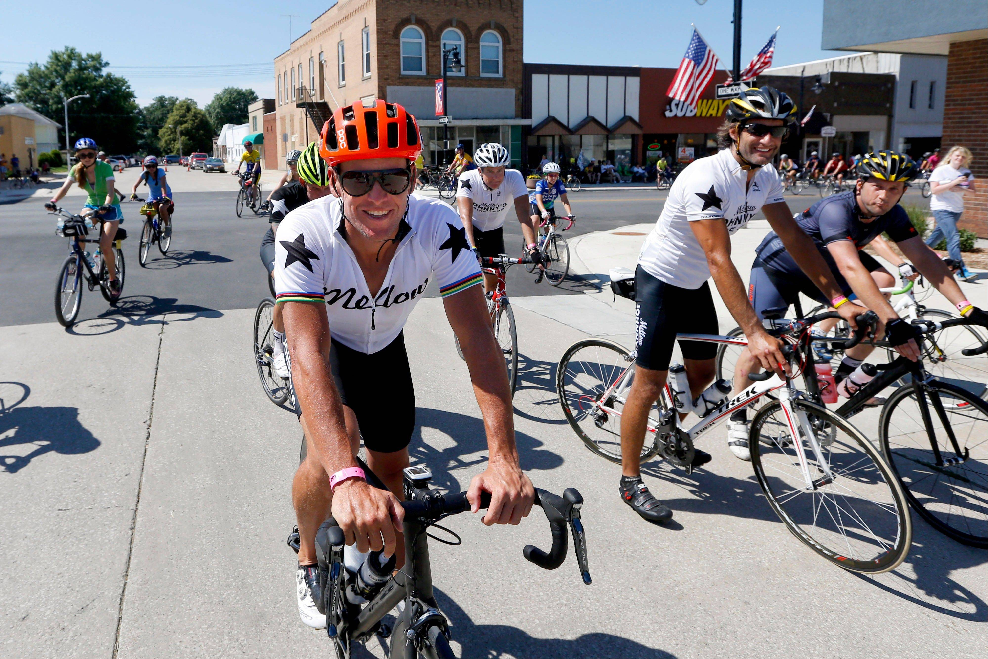 Lance Armstrong, left foreground, rides through Gutherie Center, Iowa, on Monday during RAGBRAI.