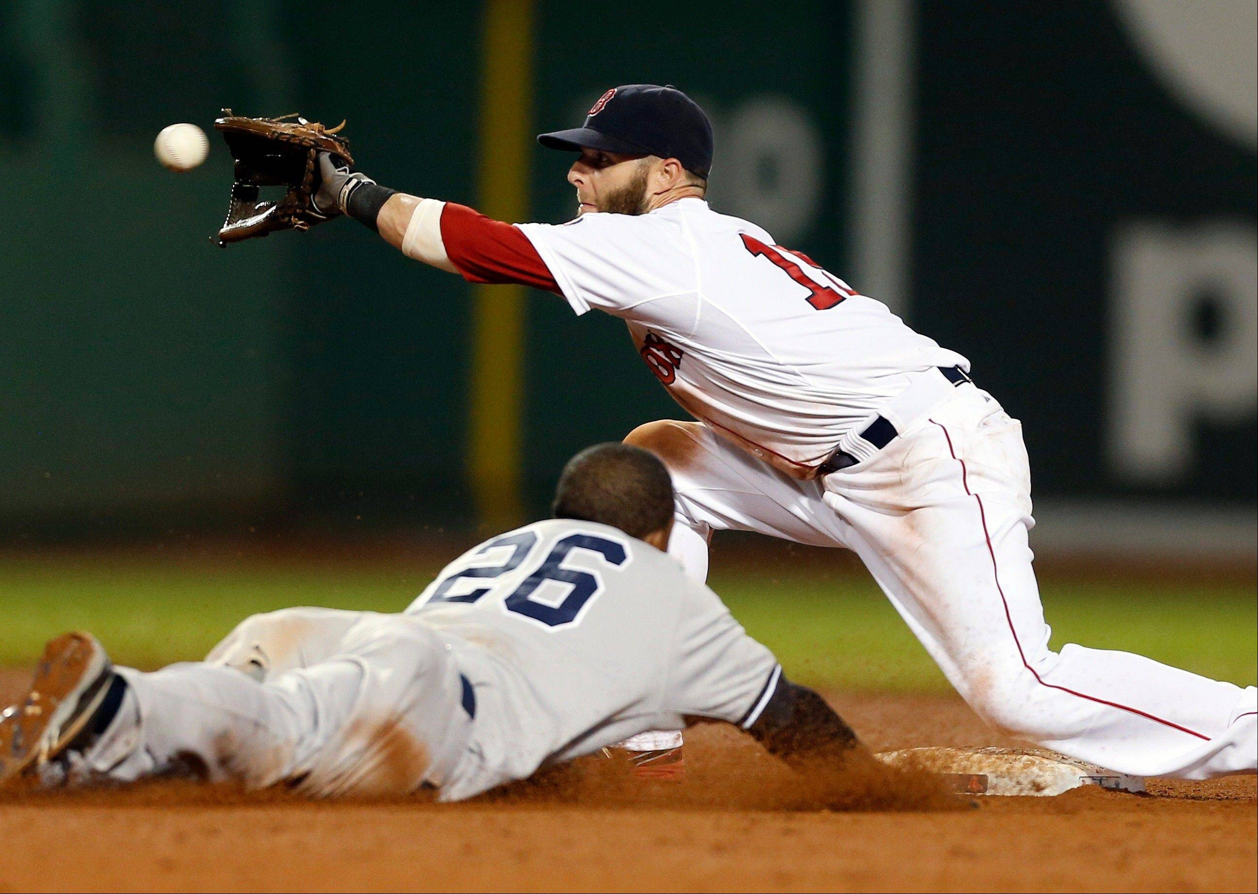 Boston Red Sox's Dustin Pedroia gets the throw before tagging out New York Yankees' Eduardo Nunez (26), who was trying to steal second base in the 11th inning of a baseball game in Boston, early Monday, July 22, 2013. The Red Sox won 8-7 in 11 innings.