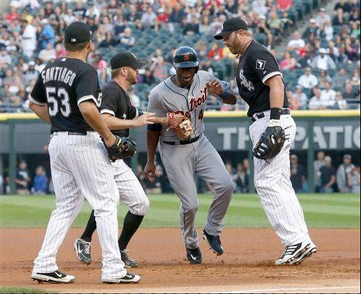 Chicago White Sox second baseman Jeff Keppinger, second from left, tags Detroit Tigers' Torii Hunter during a rundown as relief pitcher Hector Santiago and first baseman Adam Dunn watch during the first inning of a baseball game Tuesday, July 23, 2013, in Chicago. First base umpire Gary Darling called Hunter safe due to interference by Dunn on the play.