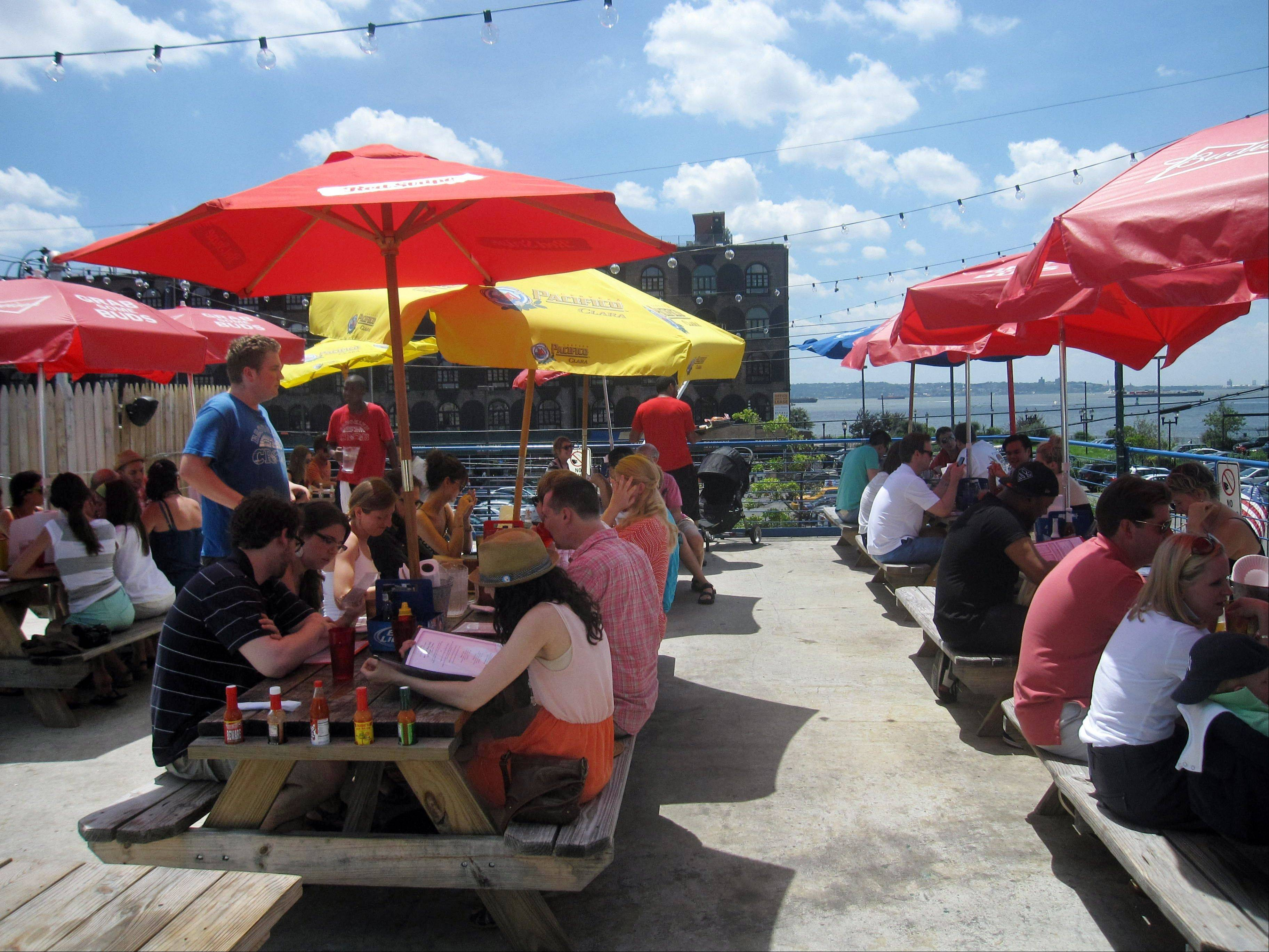 Diners eat at picnic tables with colorful umbrellas at Brooklyn Crab in Red Hook, a popular seafood eatery in a working-class industrial neighborhood in New York City's Brooklyn borough. The restaurant offers a view of the Brooklyn waterfront.