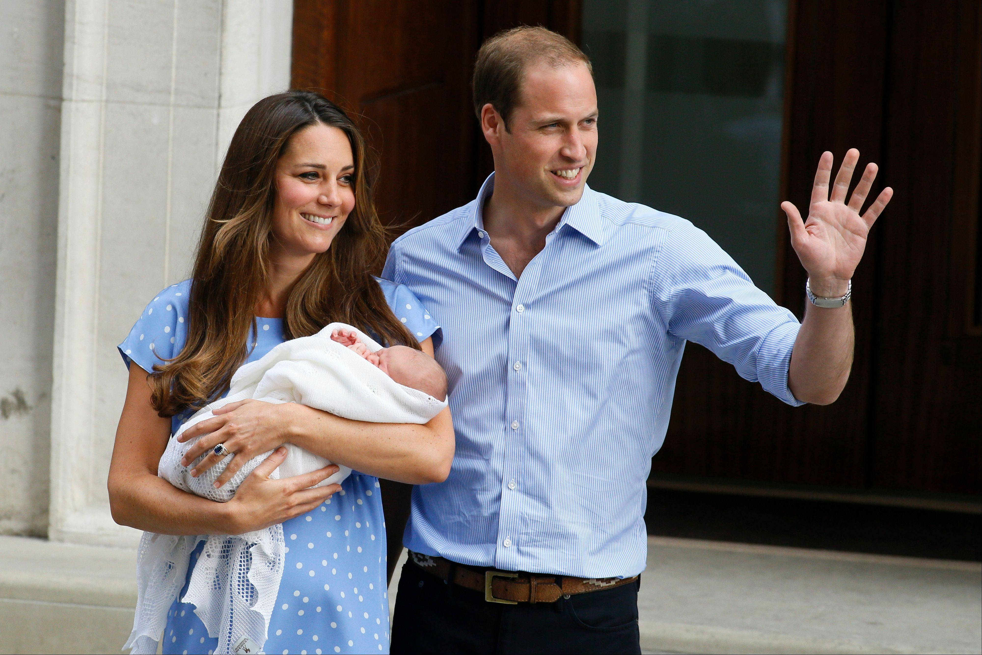 Britain's Prince William, right, and Kate, Duchess of Cambridge, hold the Prince of Cambridge, Tuesday July 23, 2013, as they pose for photographers outside St. Mary's Hospital exclusive Lindo Wing in London where the Duchess gave birth on Monday July 22. Palace officials said Wednesday that the new prince has been named George Alexander Louis.