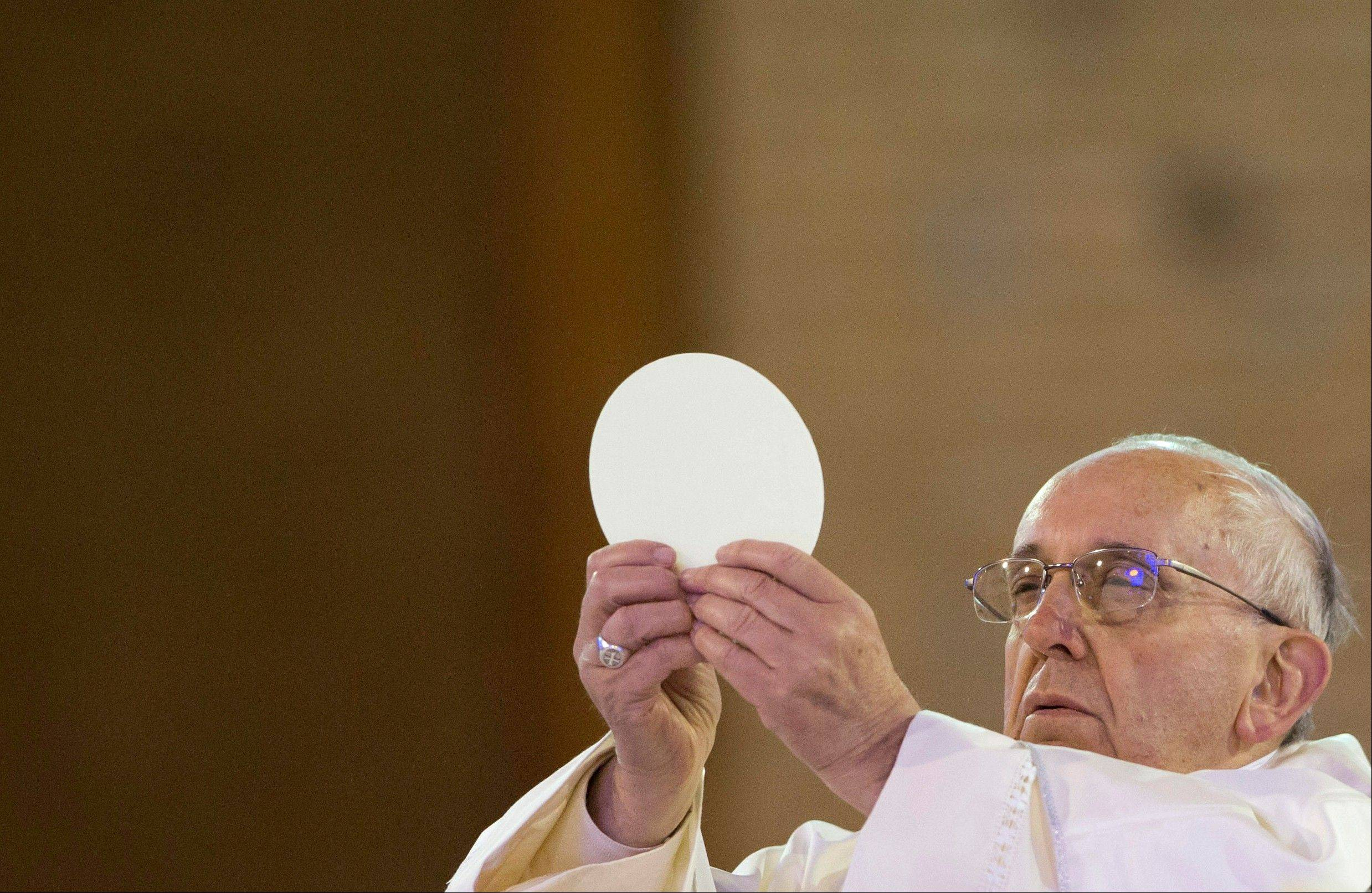 Pope Francis holds up the Eucharist as he gives Mass inside Aparecida Basilica in Aparecida, Brazil, Wednesday, July 24, 2013.
