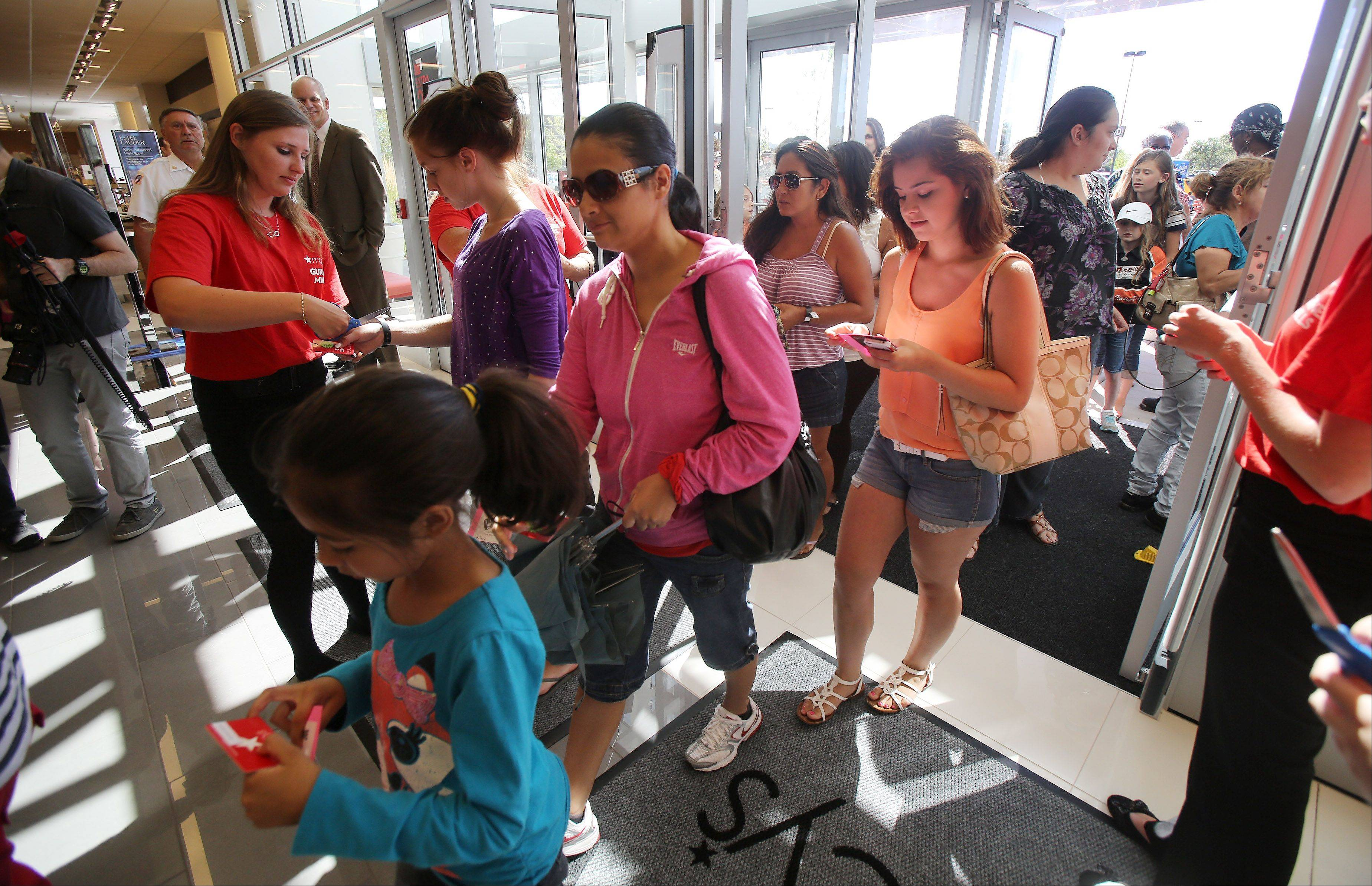 Customers receive store gift cards as the doors open for Wednesday's grand opening of Macy's in Gurnee Mills. The first 300 customers received a gift card.