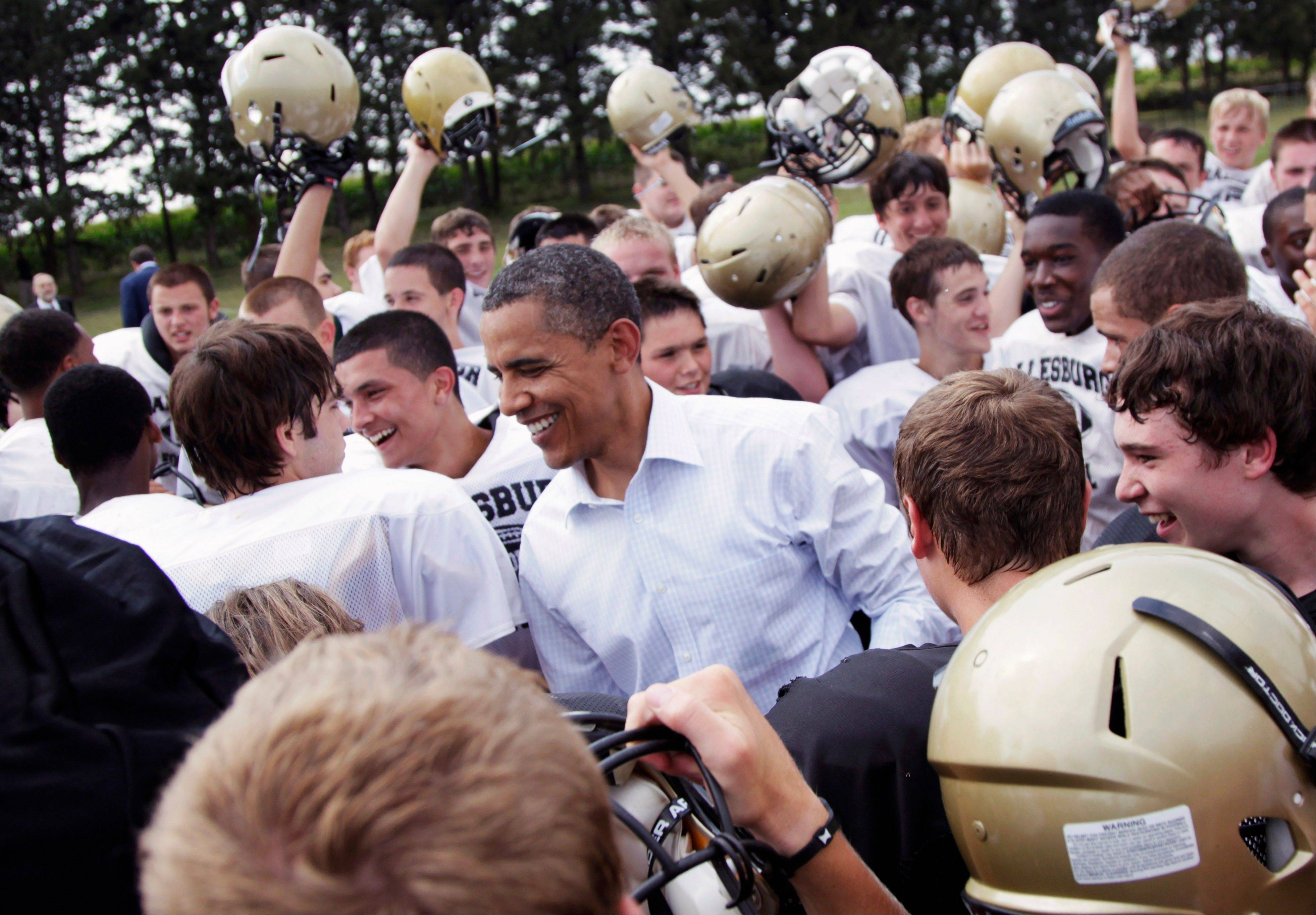 Associated PressIn this Aug. 17, 2011 photo, President Barack Obama huddles with the Galesburg High School football team in Galesburg during a three-day economic bus tour.
