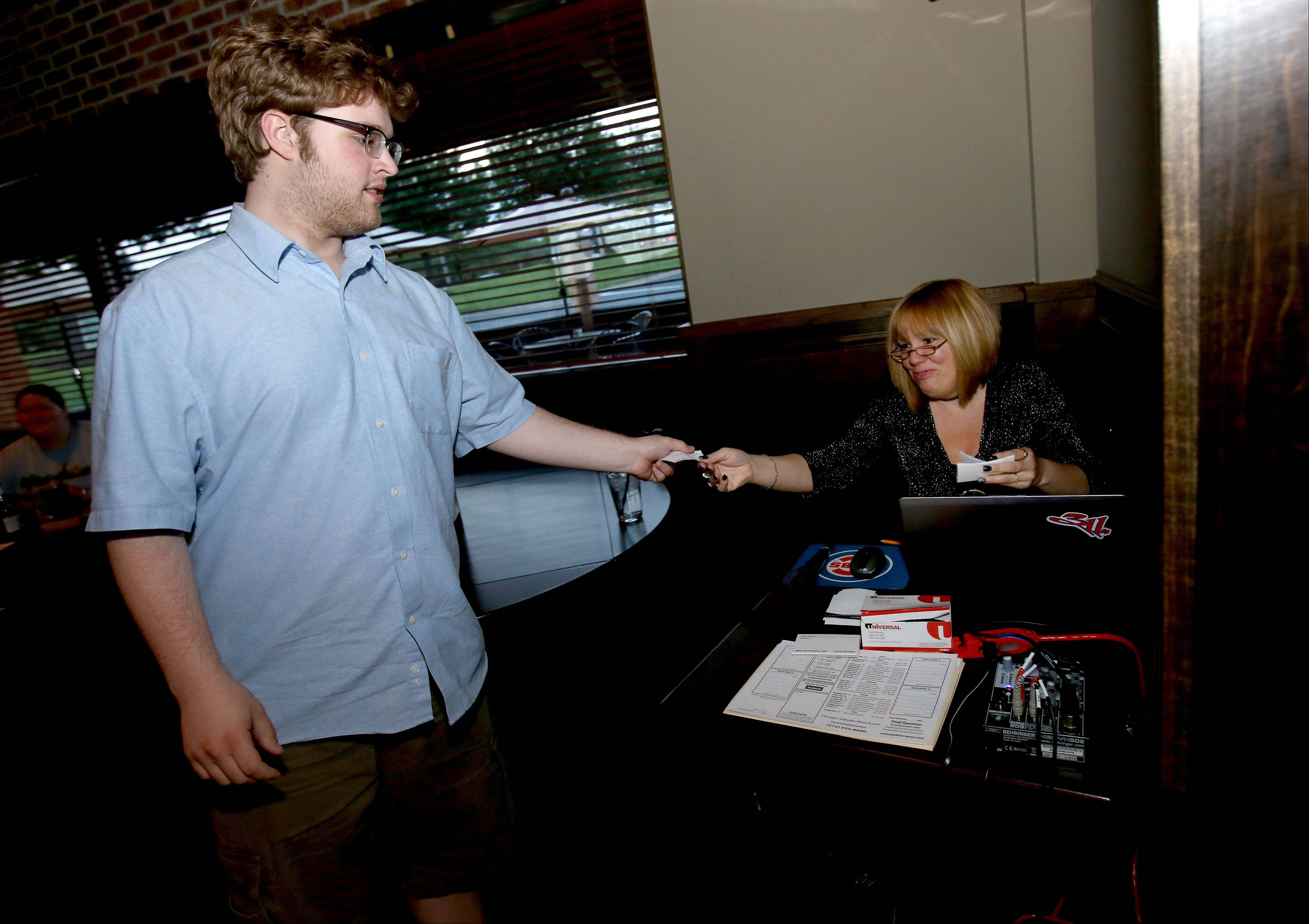 Noah Wright of Wheaton hands in his answer to Donna Breckenridge of Pub Trivia U.S.A. during Tuesday night trivia night at Warren's Ale House in Wheaton.