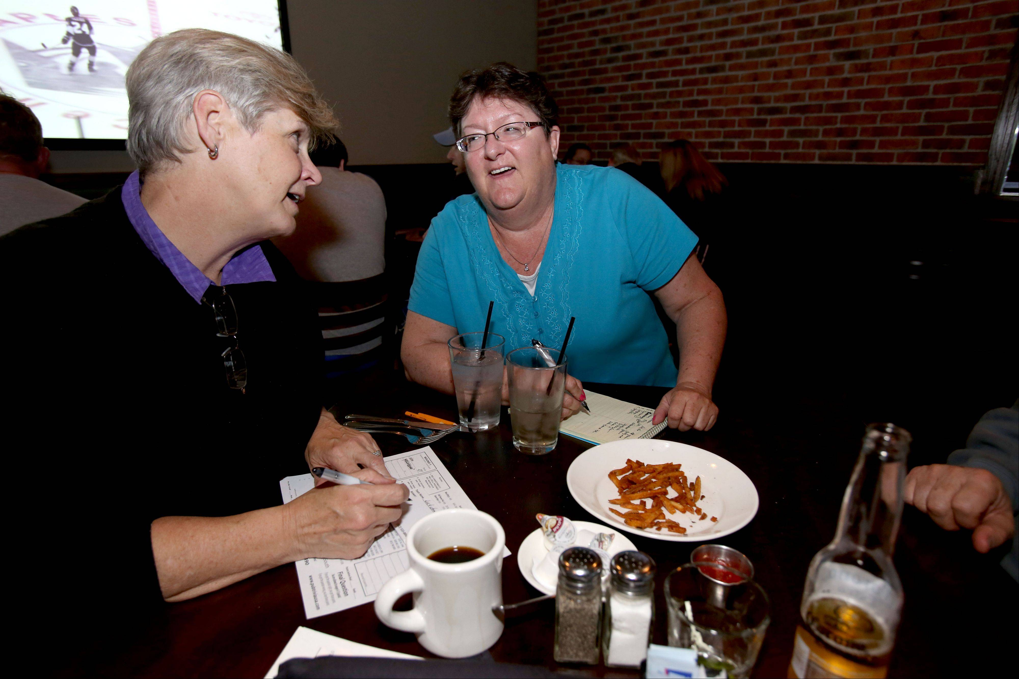 Wheaton residents Julie Mategrano, left, and Brenda Mitchell, right, try to figure out the next answer during Trivia Night at Warren's Ale House in Wheaton.