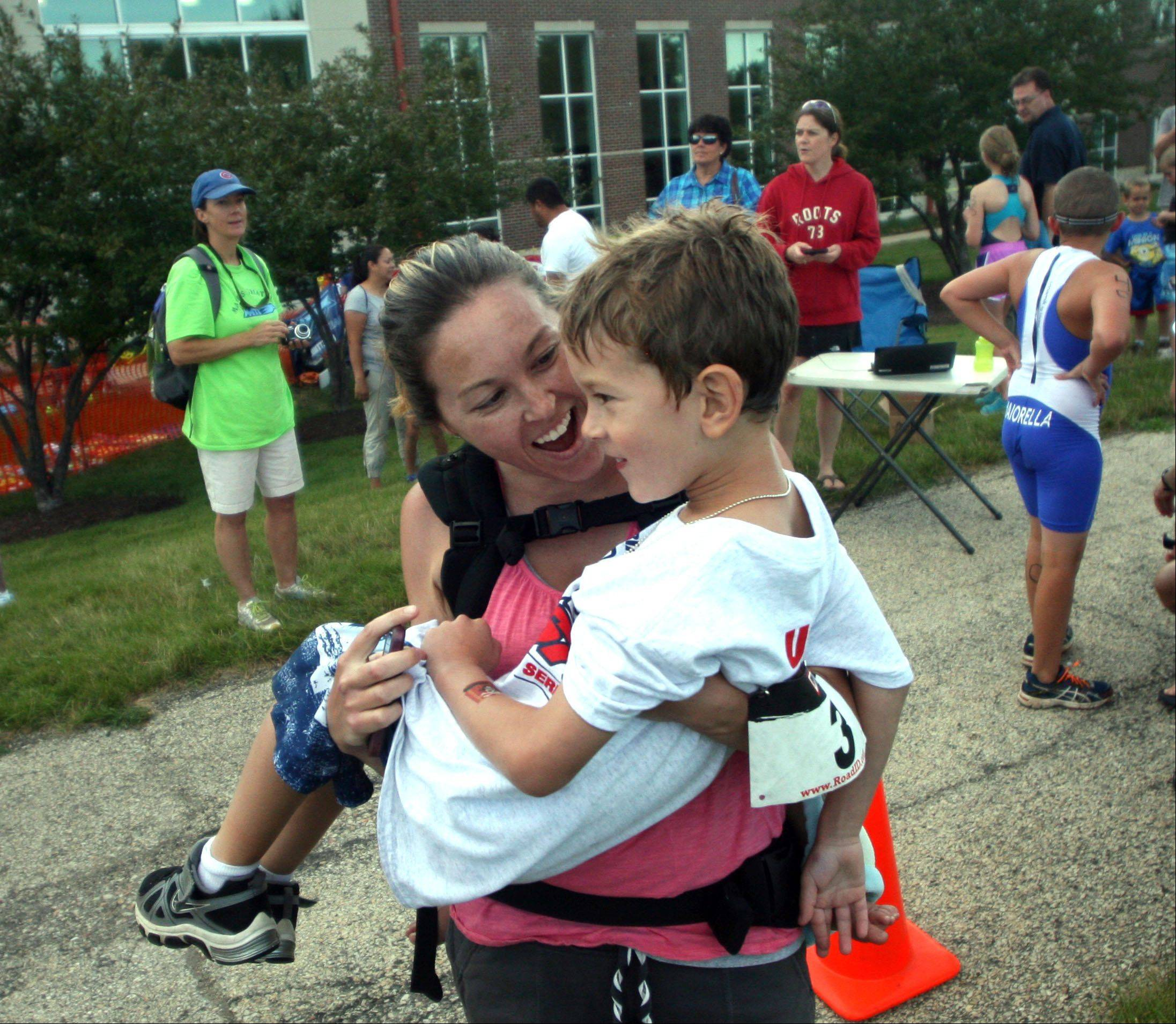 Contrell Muscari of St. Charles scoops up her son Dominic, 6, as she offers encouragement after he completed a 100-yard swim followed by a 1-km run in the Juniors event that was part of the MMTT Splash and Dash race at Cadence Fitness and Health Center in Geneva Wednesday night.