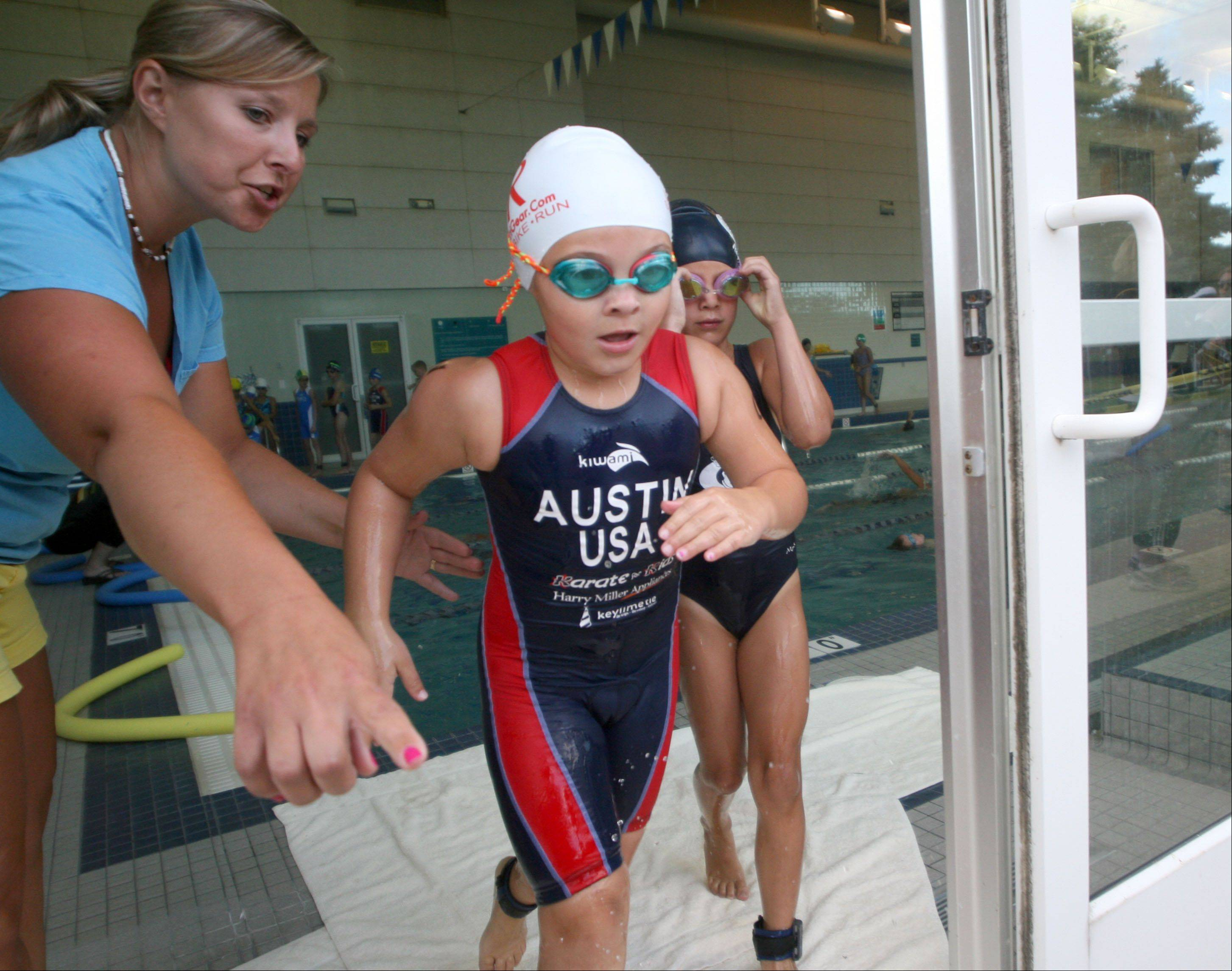 Cadence Fitness and Health Center employee Jennifer Parrilli, left, guides athletes during the Juniors event of the MMTT Splash and Dash race at Cadence Fitness and Health Center in Geneva Wednesday night.