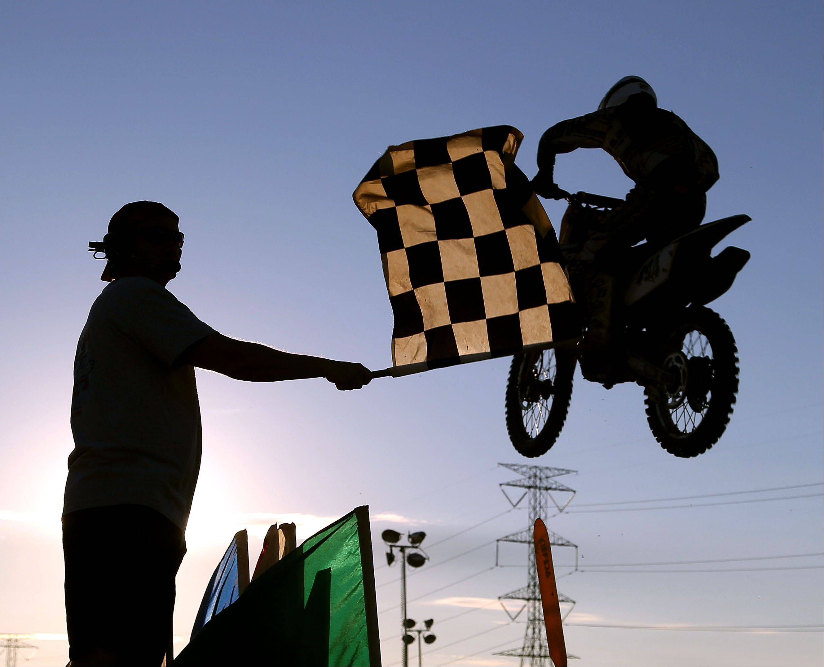 Motocross racers cross the finish line during opening day of the Lake County Fair in Grayslake Wednesday.