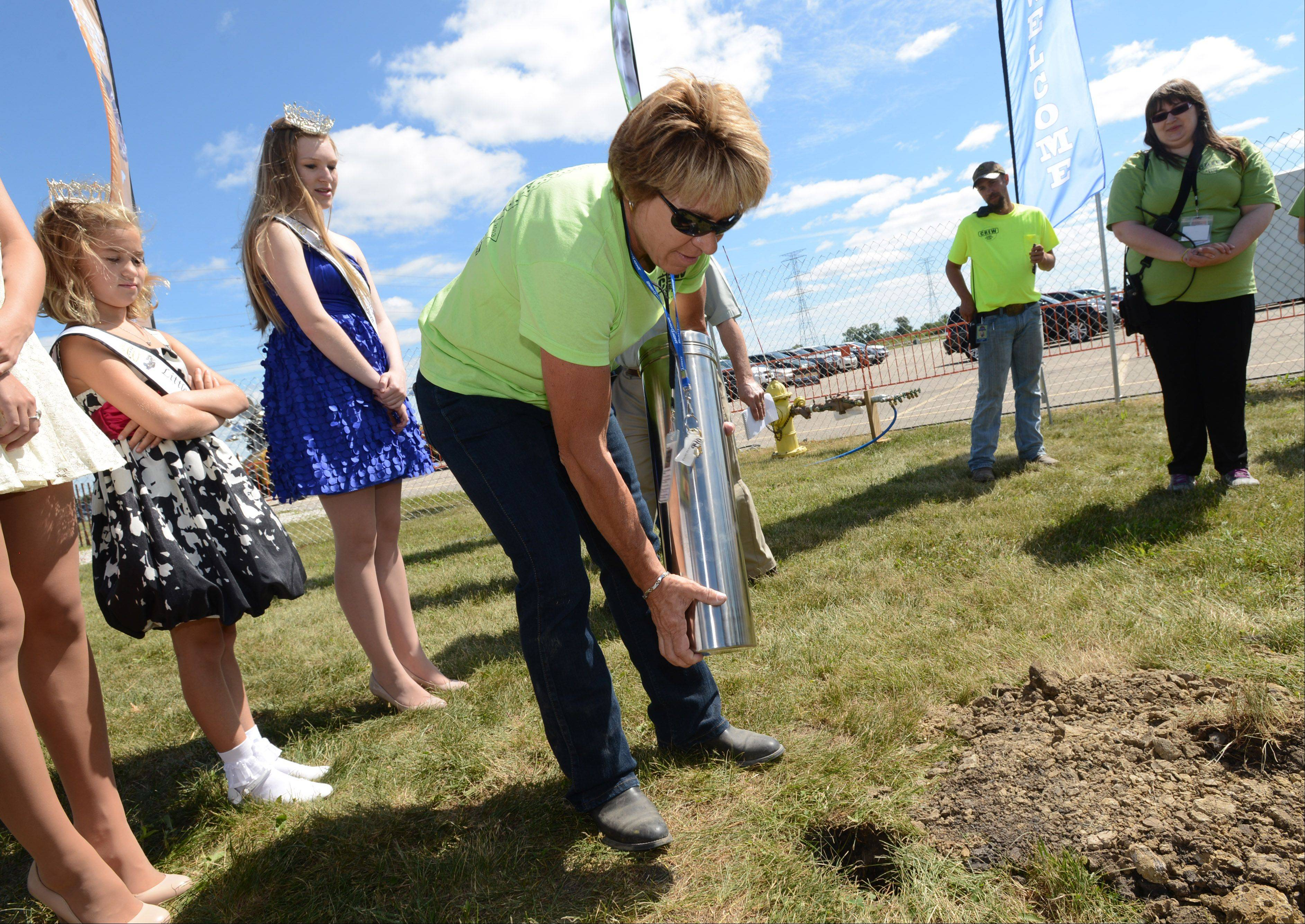 Lake County Fair board member Kelli Kepler-Yarc drops the time capsule in the hole after it was sealed with fair items Wednesday morning in Grayslake.