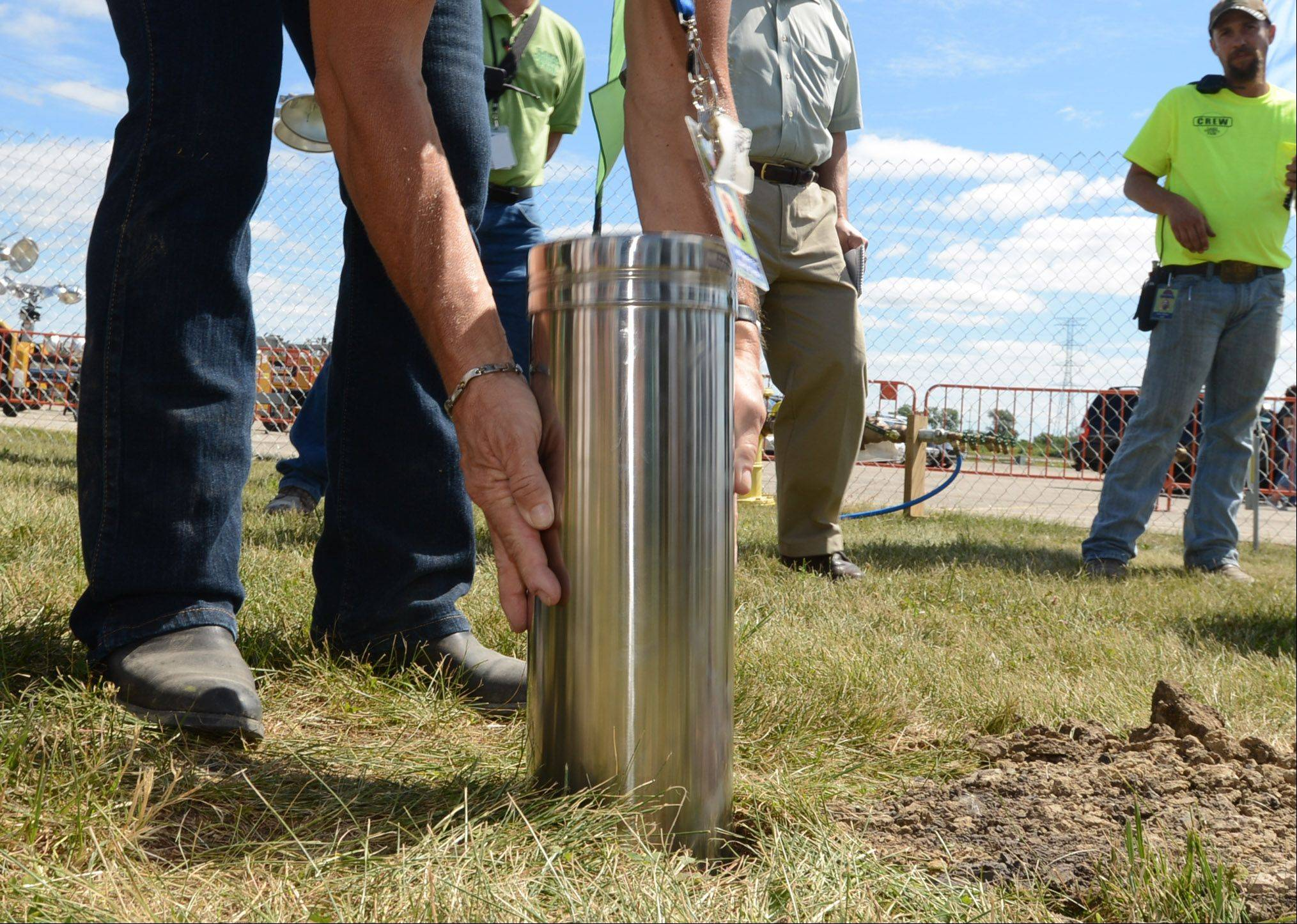 A time capsule is dropped into a hole Wednesday at the Lake County Fair in Grayslake.