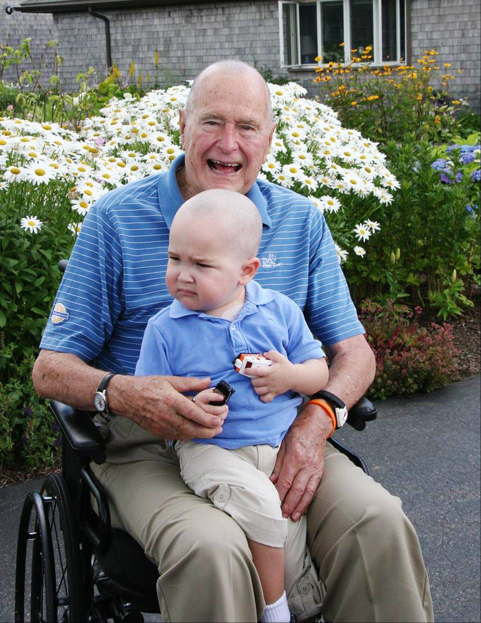 President George H.W. Bush poses with 2-year-old Patrick, last name withheld at family's request, in Kennebunkport, Maine. Bush this week joined members of his Secret Service detail in shaving his head to show solidarity for Patrick, who is the son of one of the agents. The child is undergoing treatment for leukemia and is losing his hair as a result.