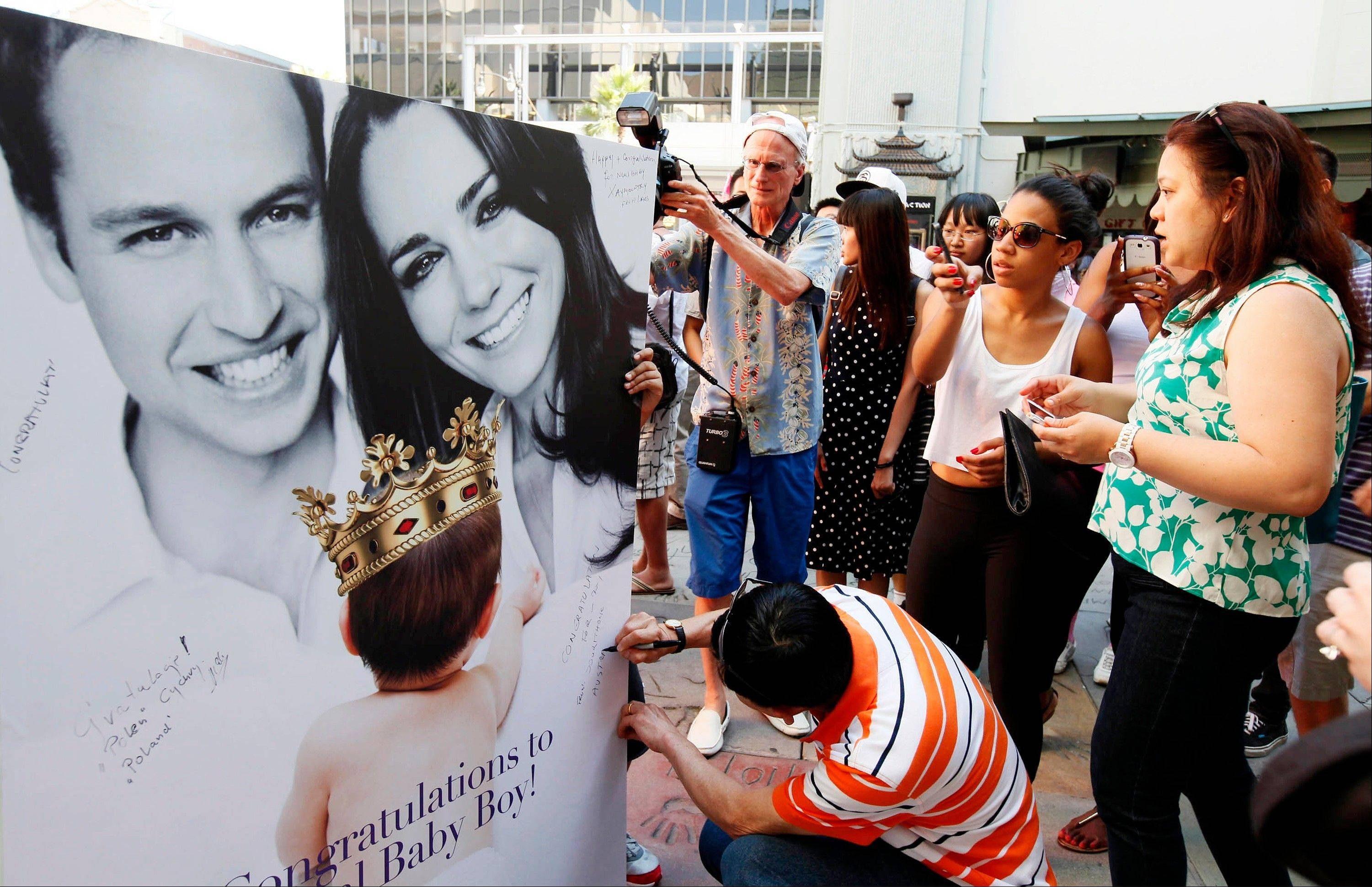 Fans and tourists sign a giant card congratulating Britain's Prince William and Kate, Duchess of Cambridge, on the birth of their baby boy Tuesday, July 23, 2013 outside the TCL Chinese Theatre in Hollywood.
