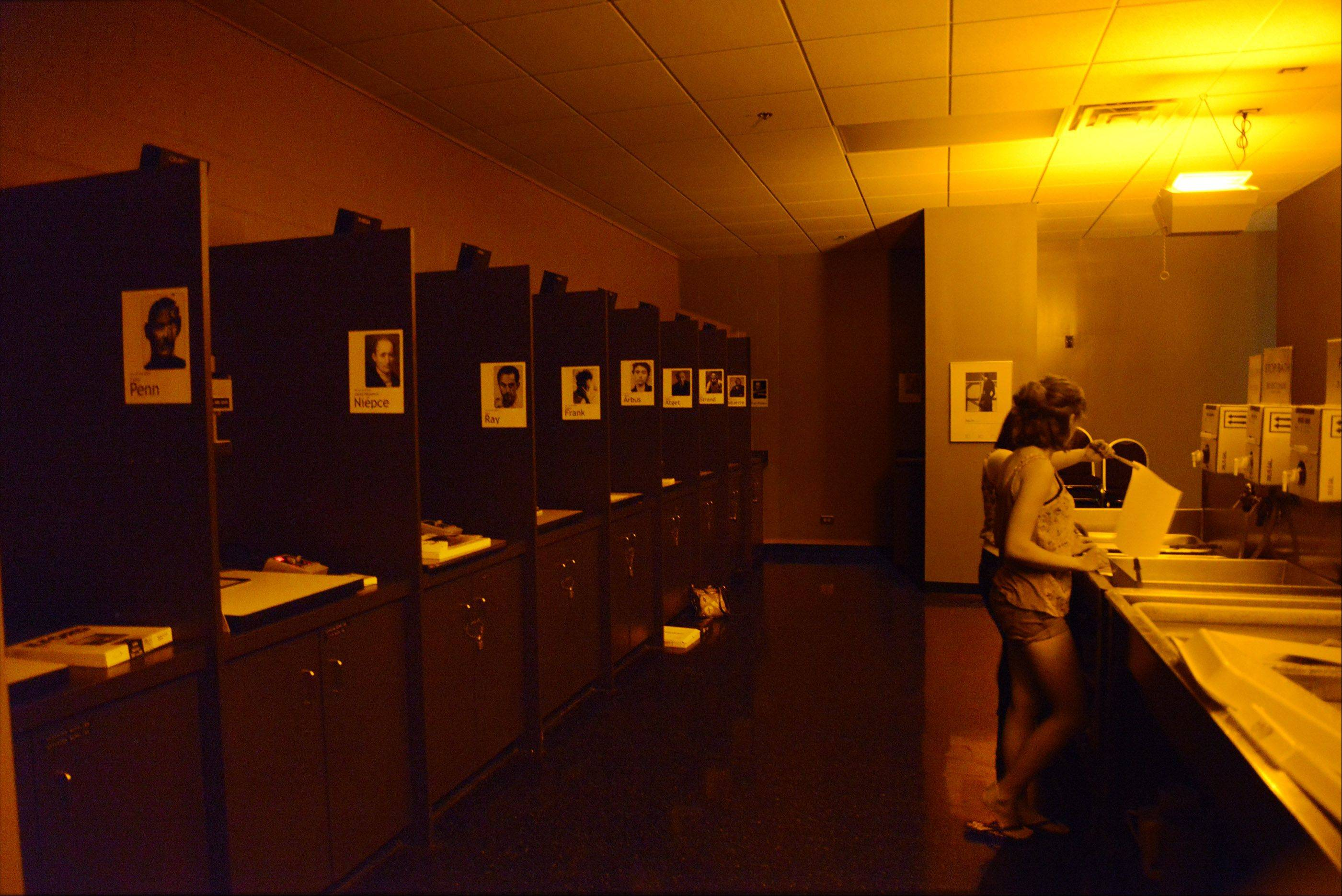 Under the warm, indirect darkroom lights, ECC photography students work with prints in chemical trays in the darkroom. At left is a row of enlargers used for printing.