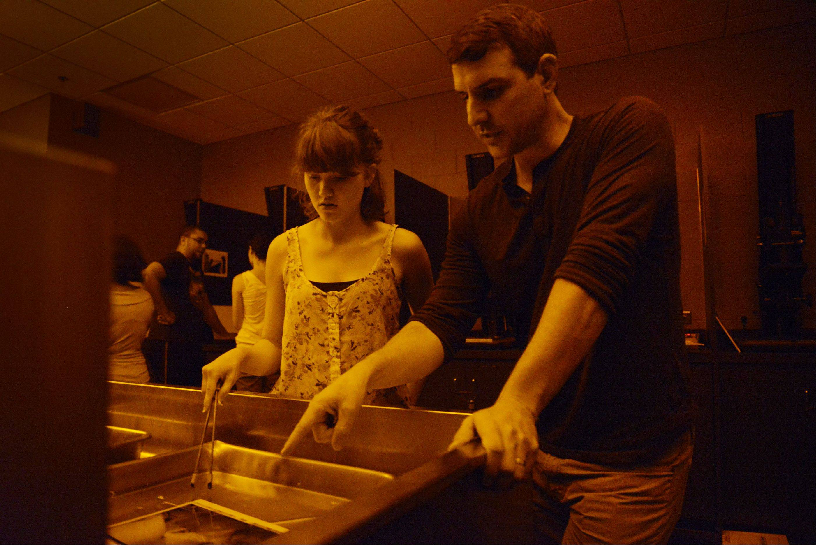 Travis Linville, assistant professor of photography, works with student Jessica Cannon in the Elgin Community College darkroom.