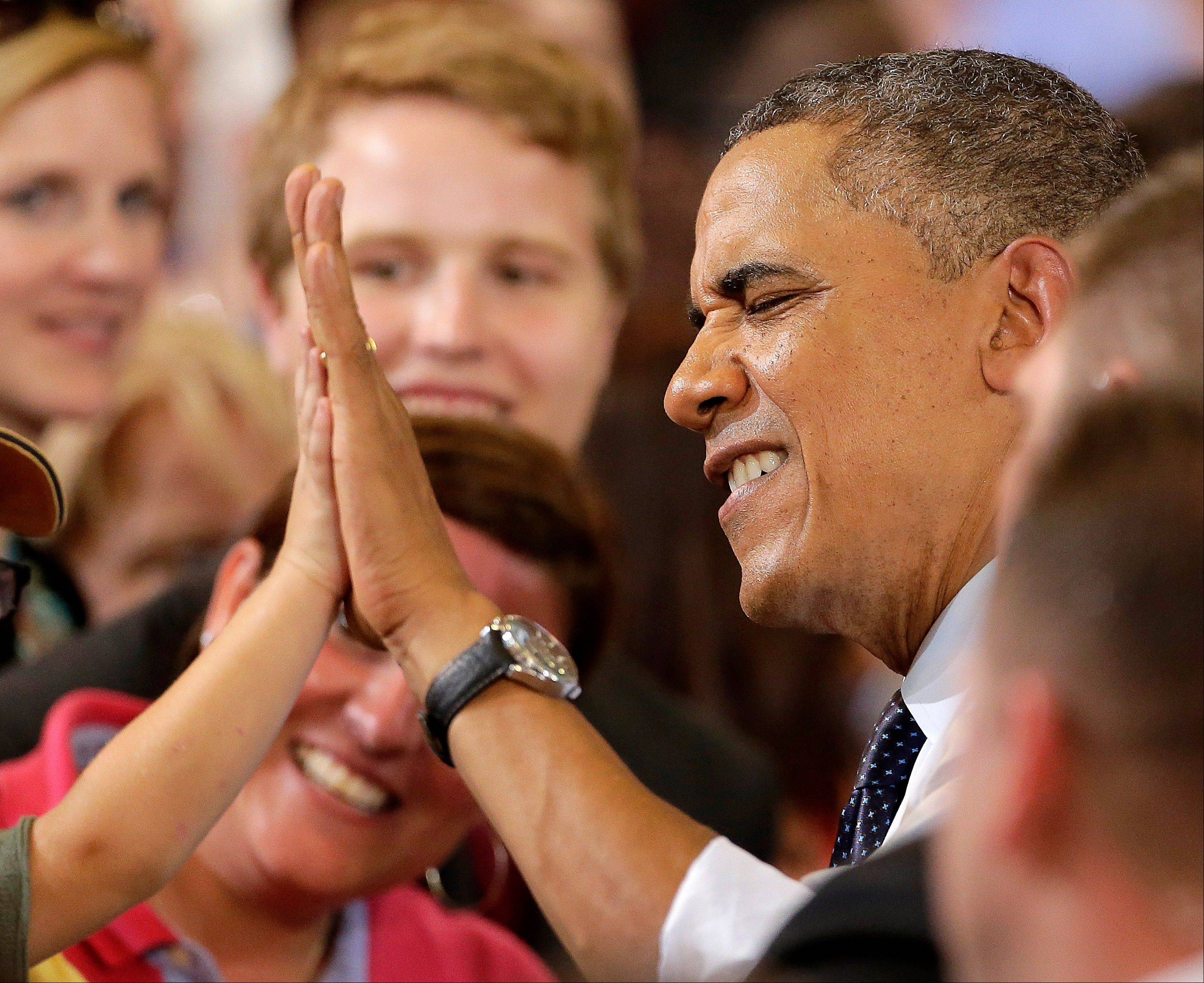 Associated Press President Barack Obama gets a high-five after speaking about the economy, Wednesday, July 24, 2013, at the University of Central Missouri in Warrensburg, Mo.
