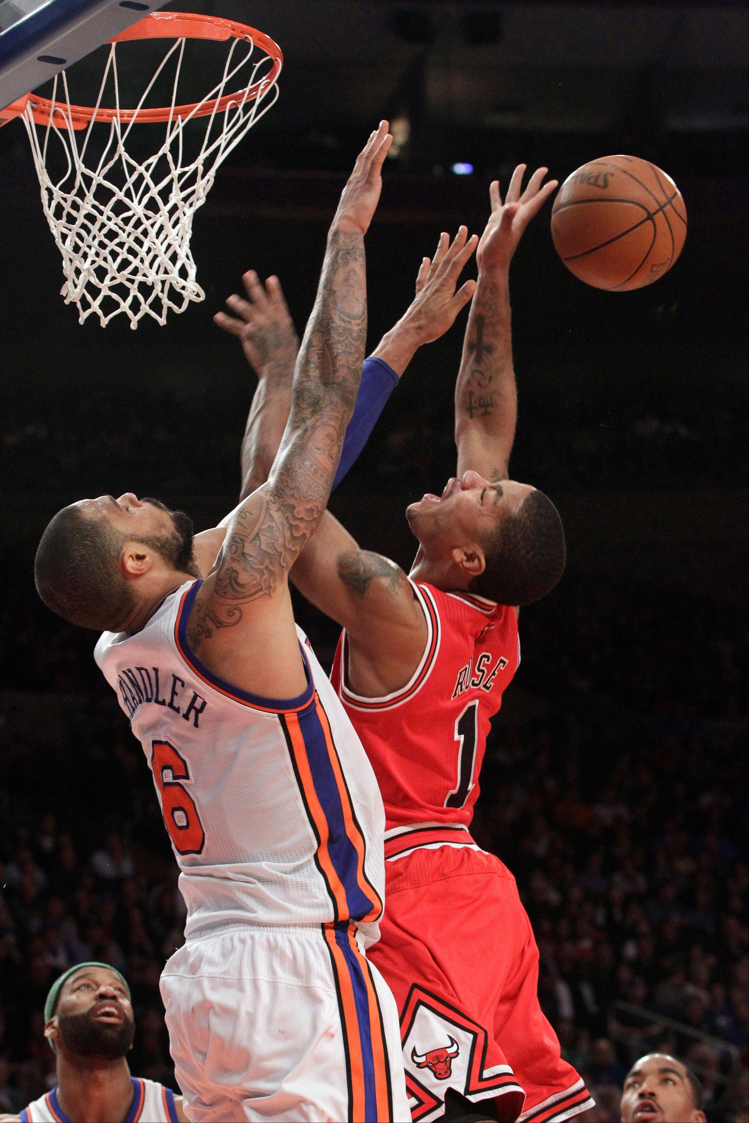 New York Knicks' Tyson Chandler, left, blocks a shot by Chicago Bulls' Derrick Rose during the second half of an NBA basketball game, Sunday, April 8, 2012, at Madison Square Garden in New York. The Knicks won 100-99 in overtime. (AP Photo/Mary Altaffer)