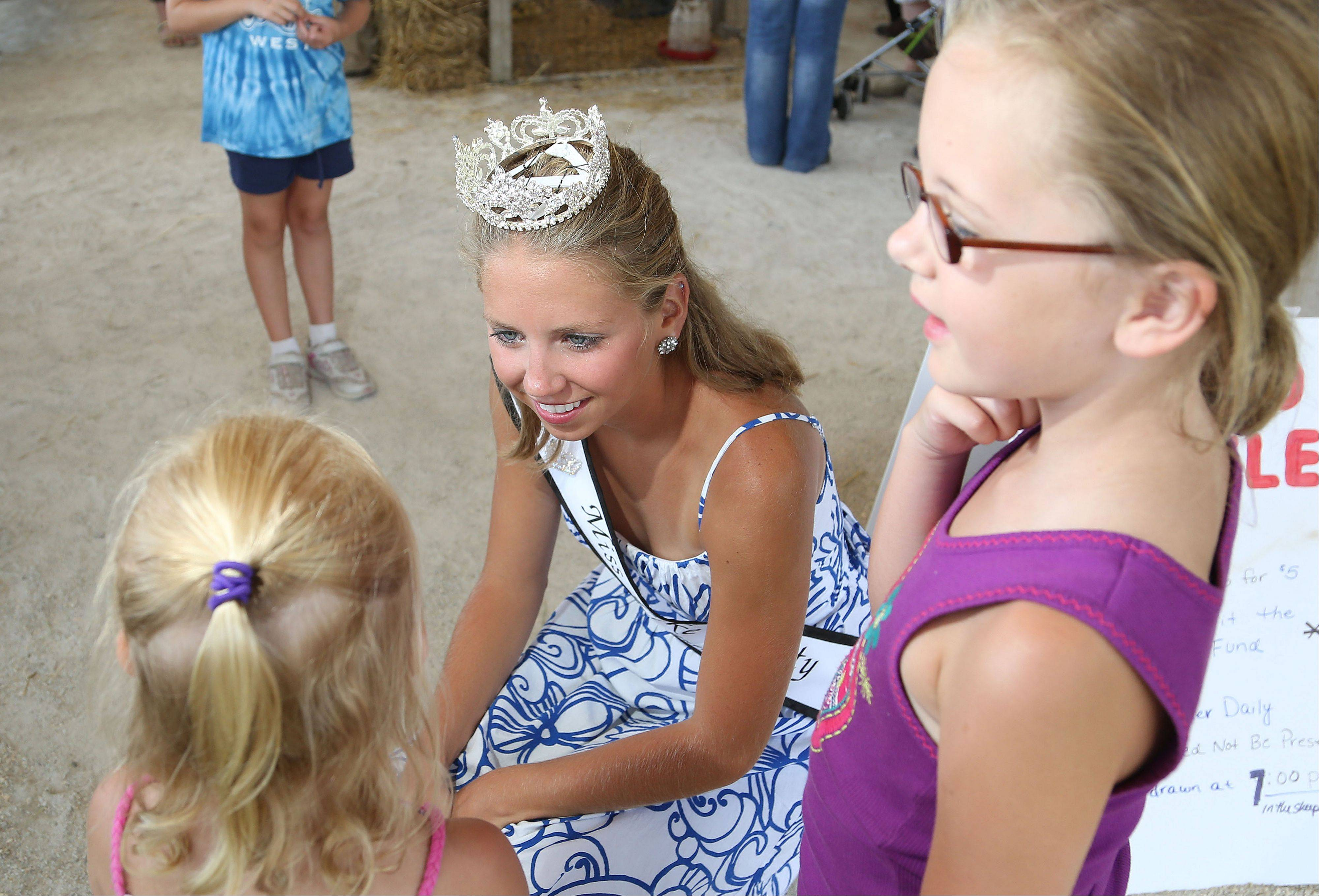 Newly-crowned Miss Lake County Fair Queen 21-year-old Meghan Opolka of Antioch talks with 4-year-old Whitney Walker, left, and her sister, 7-year-old Sydney Walker at the Lake County Fair Thursday.