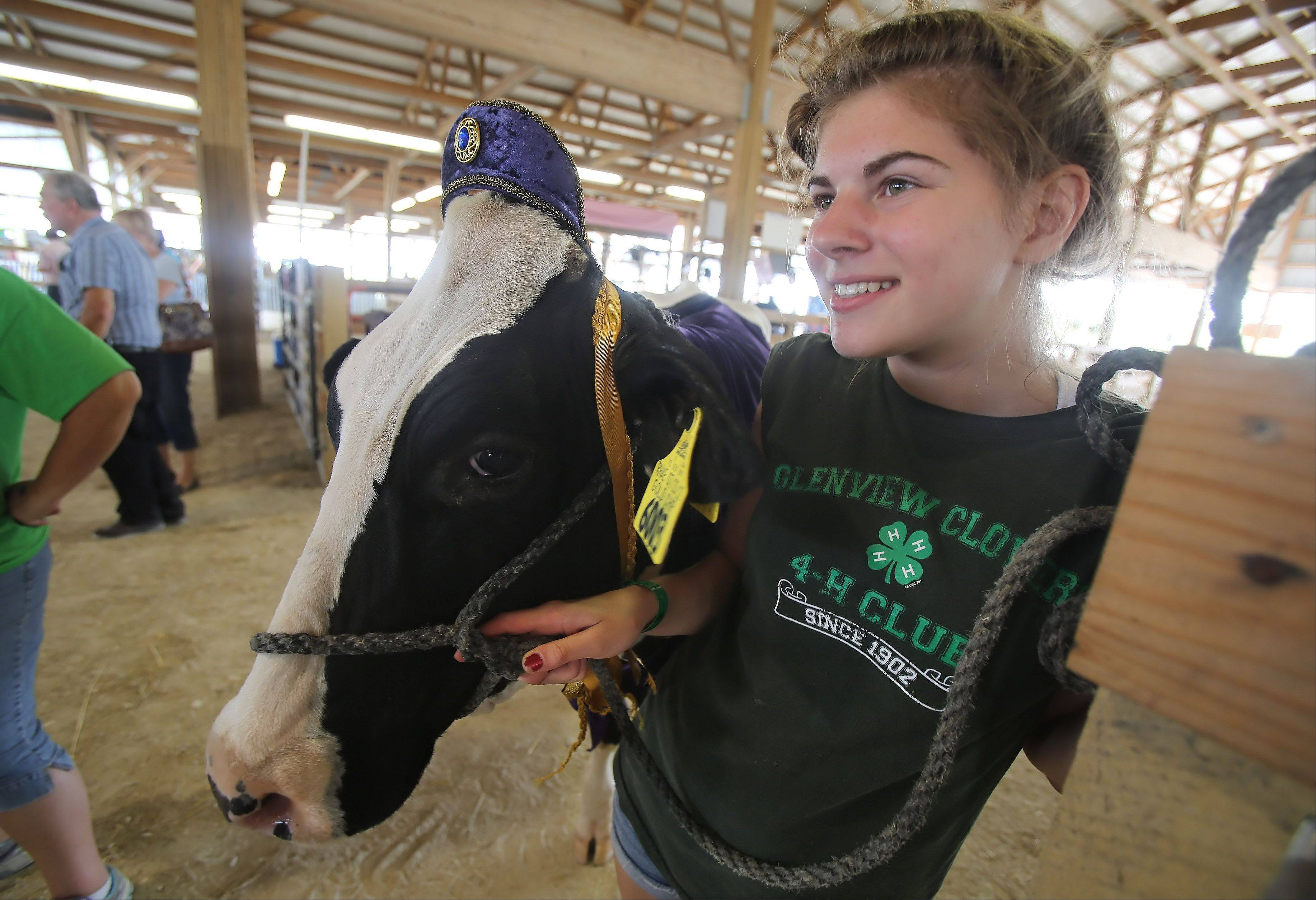 Anna Madsen, 15, of Glenview stands with her cow dressed as the Royal Baby as they wait Livestock Costume Contest during the Lake County Fair Thursday at the Lake County Fairgrounds in Grayslake.