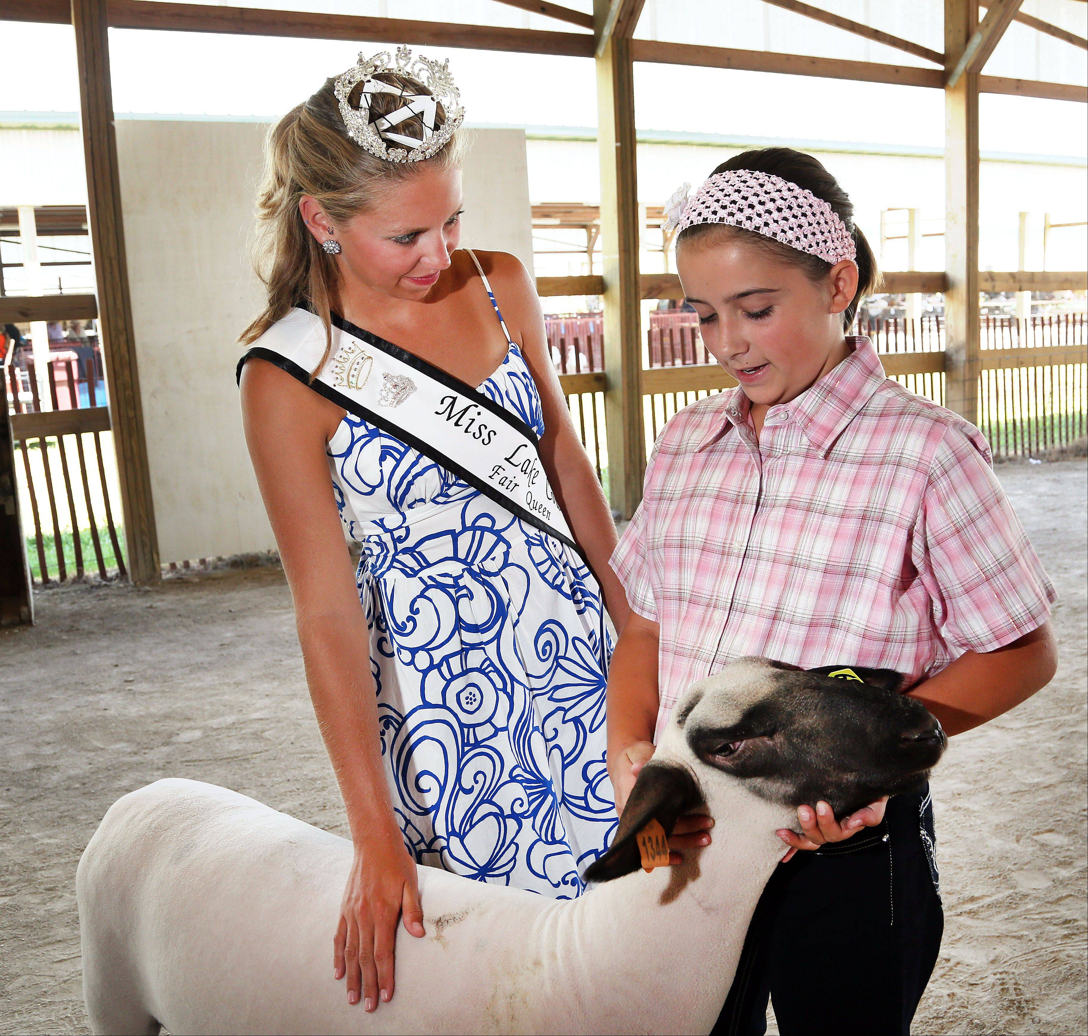 Newly-crowned Miss Lake County Fair Queen 21-year-old Meghan Opolka of Antioch talks with 10-year-old Kendra Dilg of Pleasant Prairie, Wisconsin after her lamb won grand champion in the open competition at the Lake County Fair in Grayslake Thursday.