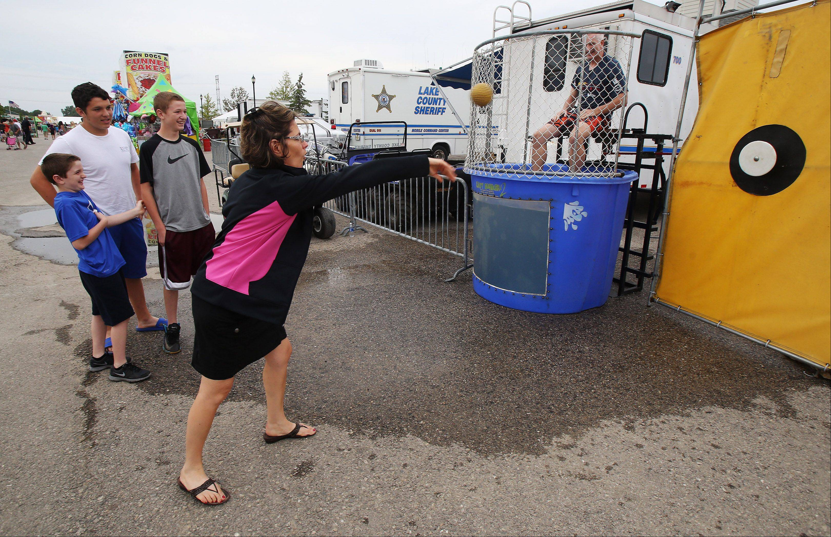 Irene Curran of Libertyville throws the ball to try and dunk her husband Lake County Sheriff Mark Curran in the dunk tank sponsored by the Lake County Sheriff's Department Thursday at the Lake County Fairgrounds in Grayslake. The money raised will be donated to Special Olympics Illinois.