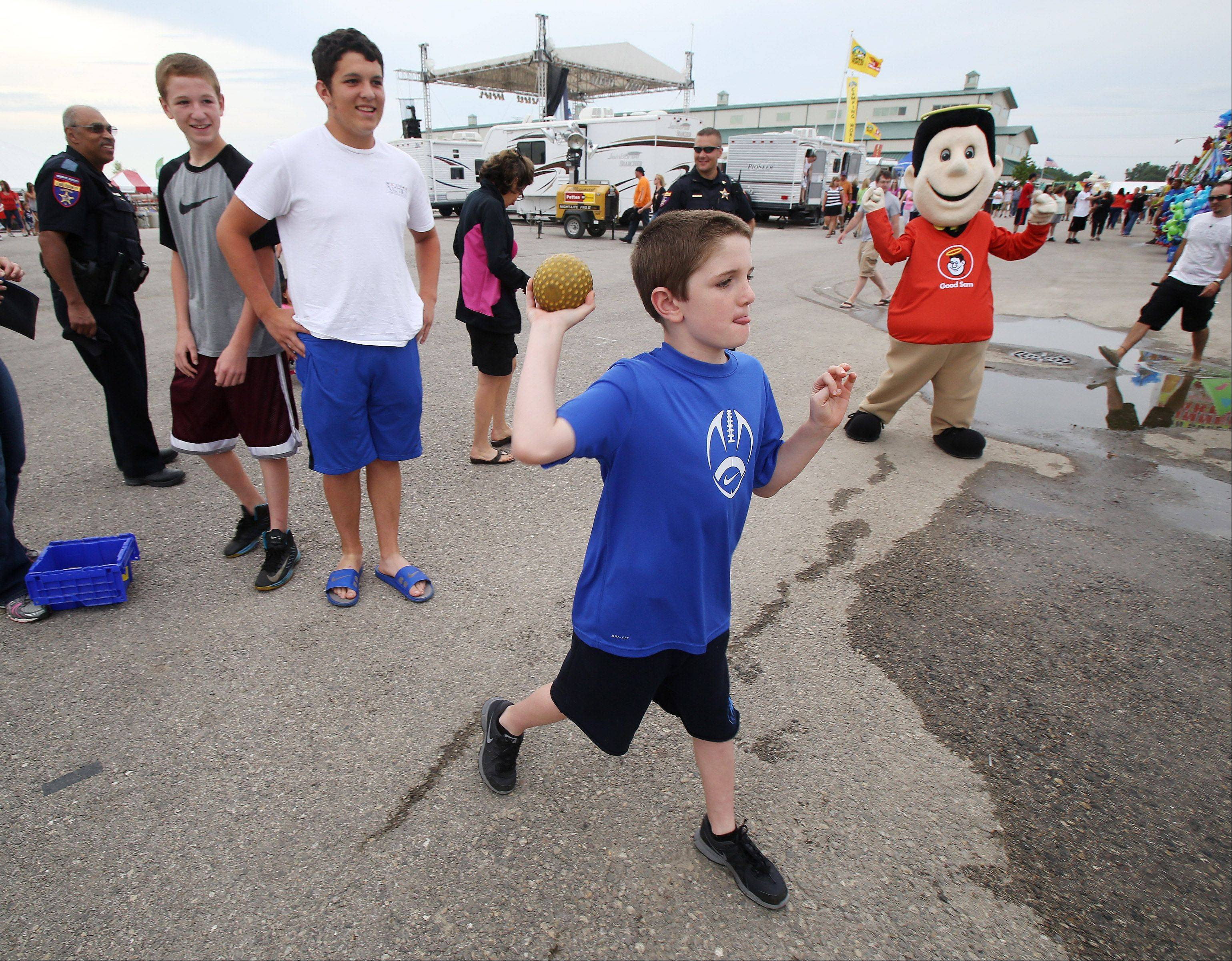 Peter Curran, 9, of Libertyville throws the ball to try and dunk his dad, Lake County Sheriff Mark Curran, in the dunk tank sponsored by the Lake County Sheriff's Department Thursday at the Lake County Fairgrounds in Grayslake. The money raised will be donated to Special Olympics Illinois. His brothers Mark, 15, and George, 14 stand in the background waiting their turns to throw.