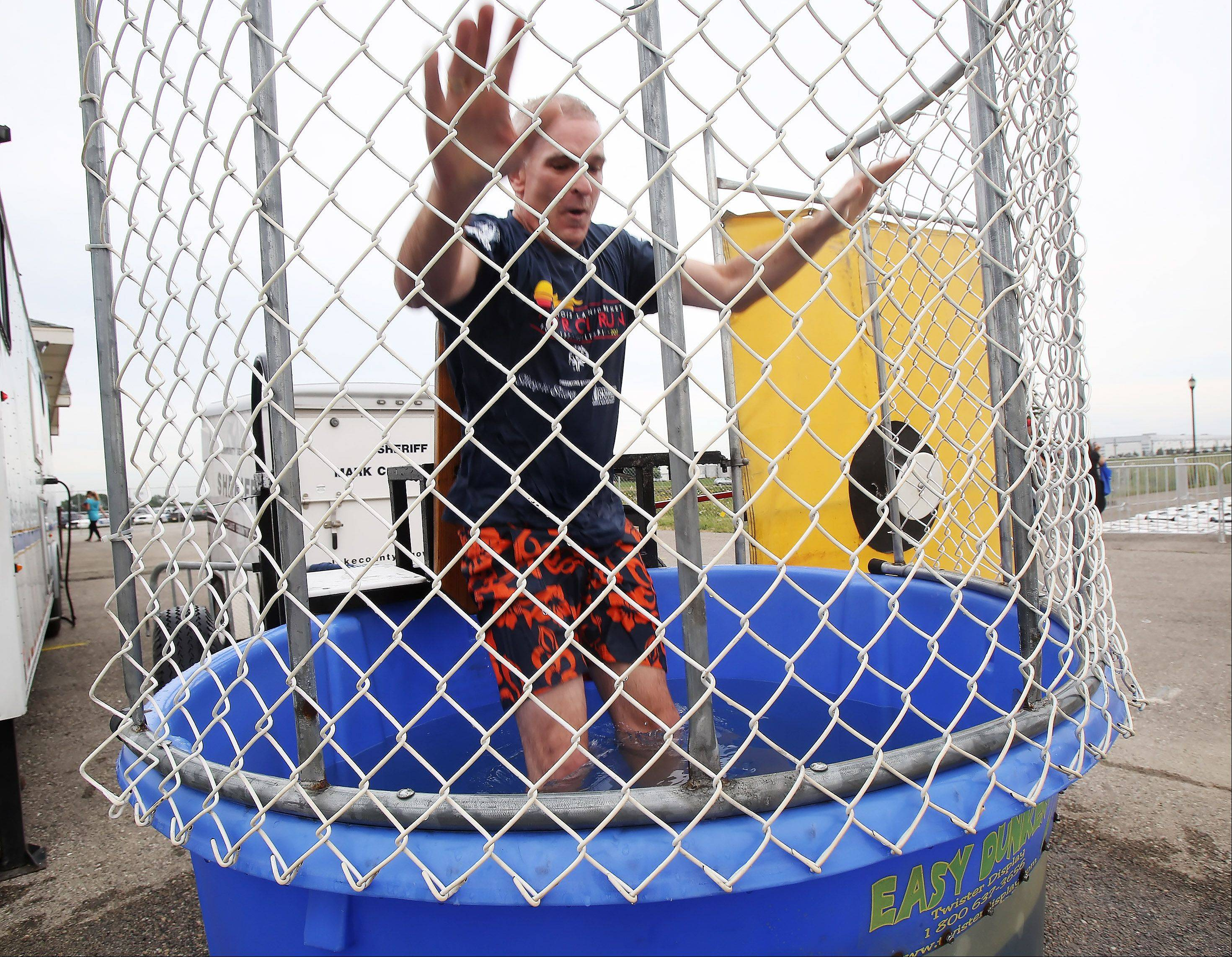 Lake County Sheriff Mark Curran falls in the water after the target was hit at the dunk tank sponsored by the Lake County Sheriff's Department Thursday at the Lake County Fairgrounds in Grayslake. The money raised will be donated to Special Olympics Illinois.