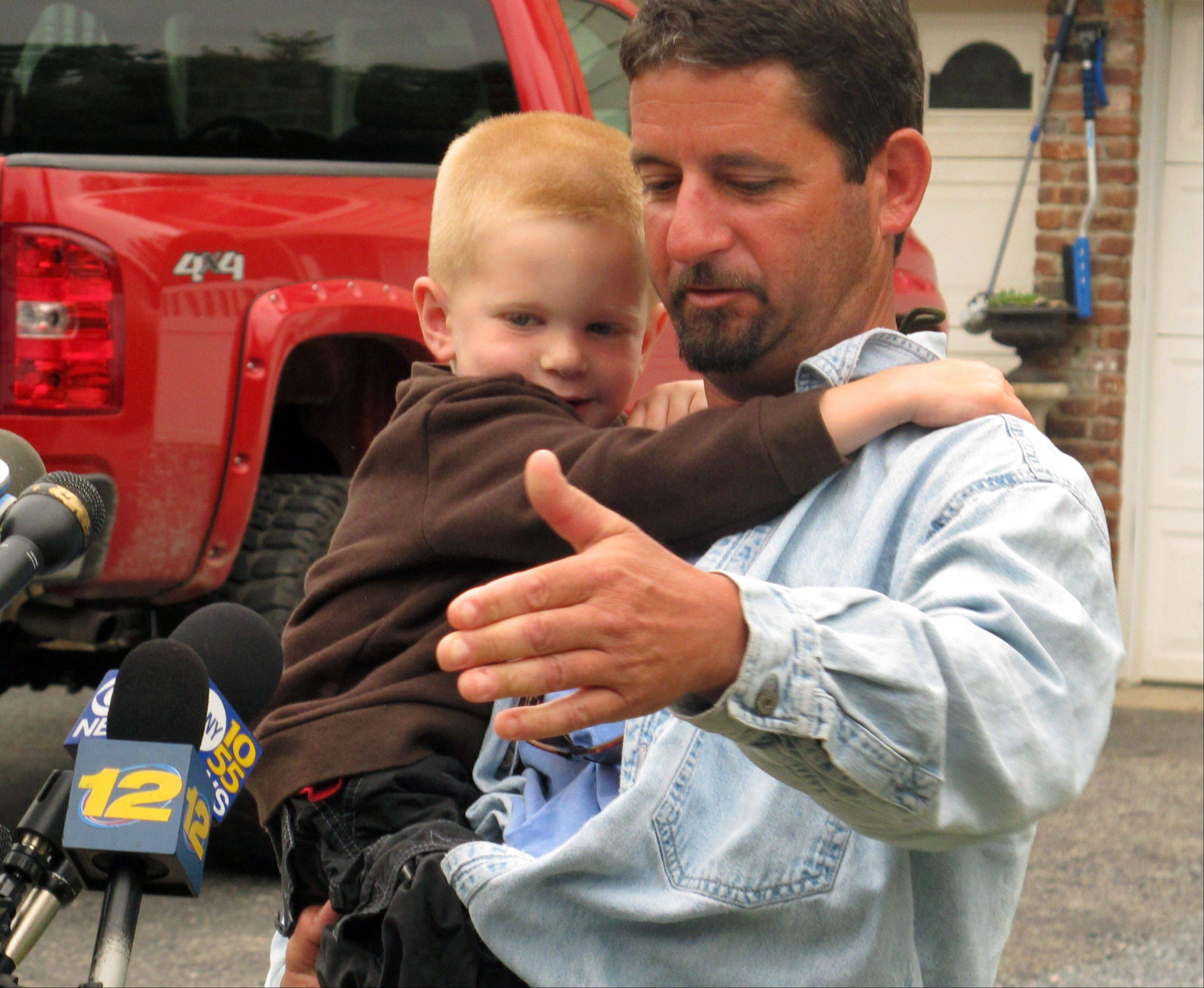 John Aldridge holds his nephew Jake after returning to his parents' home Thursday in Oakdale, N.Y.