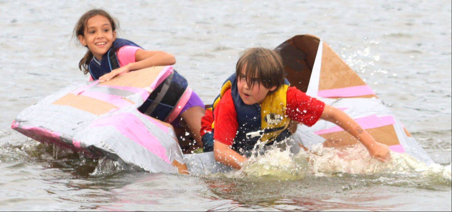"Lofton Evitts, right, paddles the ""Pop Tart Cat"" with teammate Tava Matesi, 9, of Algonquin during the Cardboard Boat Regatta juniors race as part of Founders' Days festivities on the Fox River in Algonquin Thursday night."
