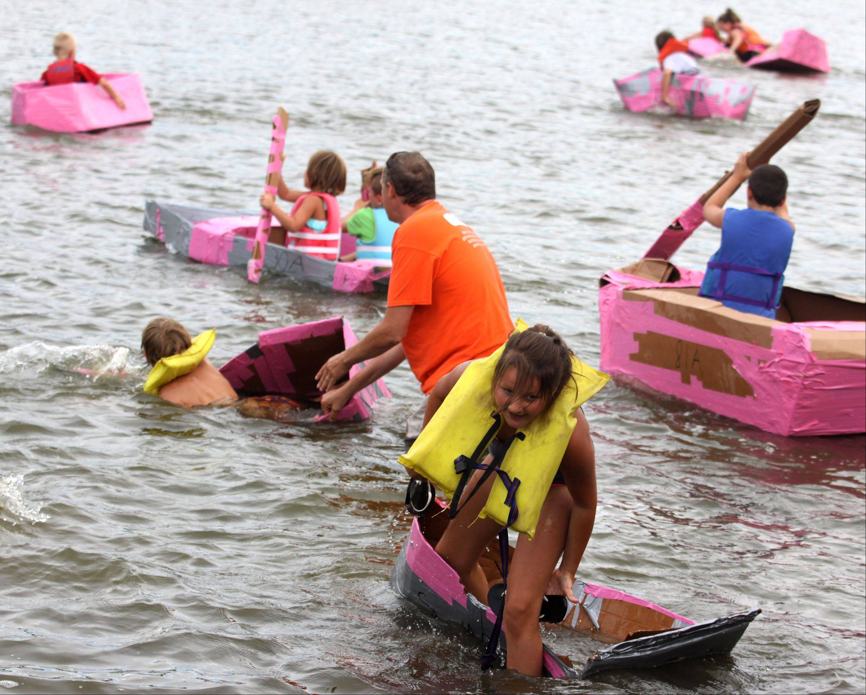 Participants slog back to shore just after the start of the Cardboard Boat Regatta juniors race as part of Founders' Days festivities on the Fox River in Algonquin Thursday night.