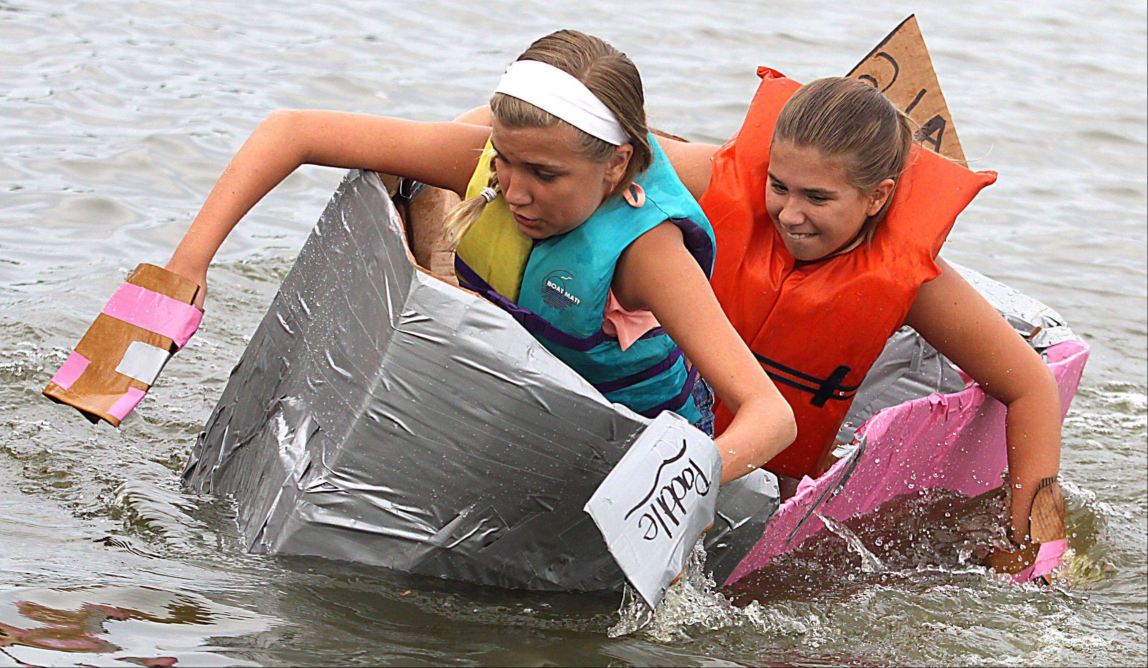 "Alaina Moran, 12, of Lake in the Hills, left, tries to keep the ""SS Starbucks"" craft afloat with her sister Alyssa, 9, during the Cardboard Boat Regatta juniors race as part of Founders' Days festivities on the Fox River in Algonquin Thursday night."