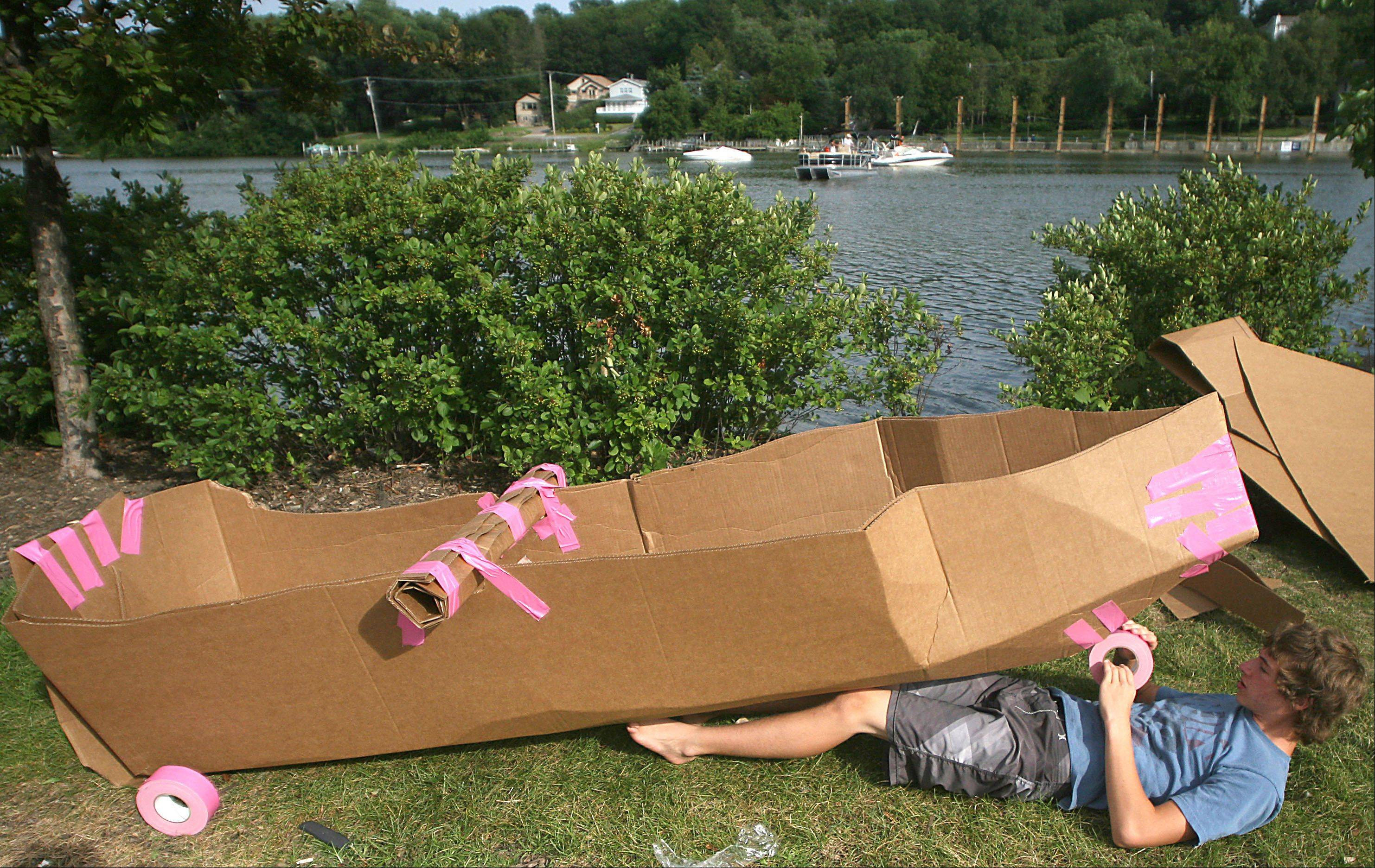 "James McDonnell, 15, of Algonquin builds his boat ""Riptide"" during the Cardboard Boat Regatta as part of Founders' Days festivities on the Fox River in Algonquin Thursday night."