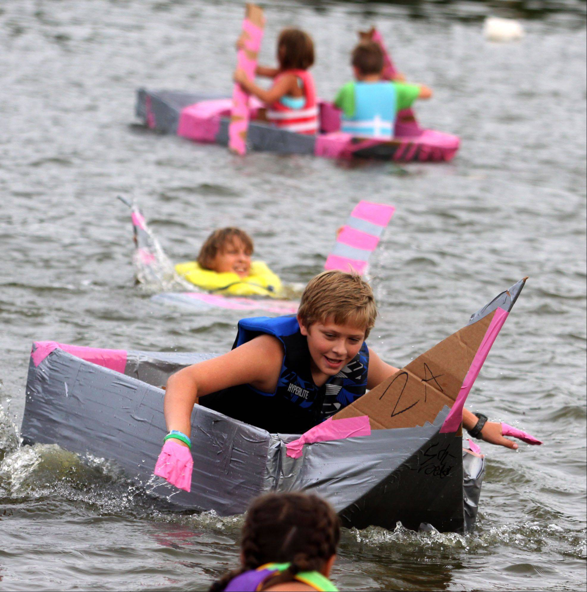 His hands fashioned into duct-tape paddles, ten-year-old Aaron Kirk of Algonquin places first during the Cardboard Boat Regatta juniors race as part of Founders' Days festivities on the Fox River in Algonquin Thursday night.