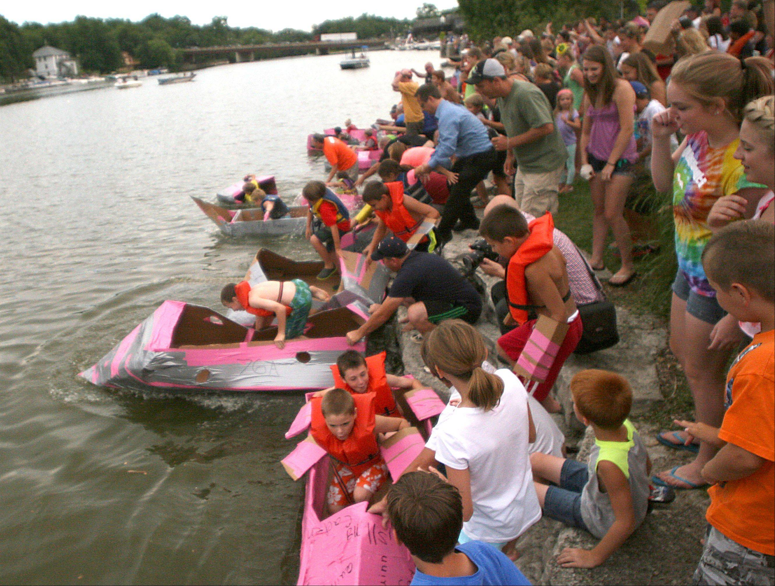 Participants launch at the start of the juniors race during the Cardboard Boat Regatta as part of Founders' Days festivities on the Fox River in Algonquin Thursday night.