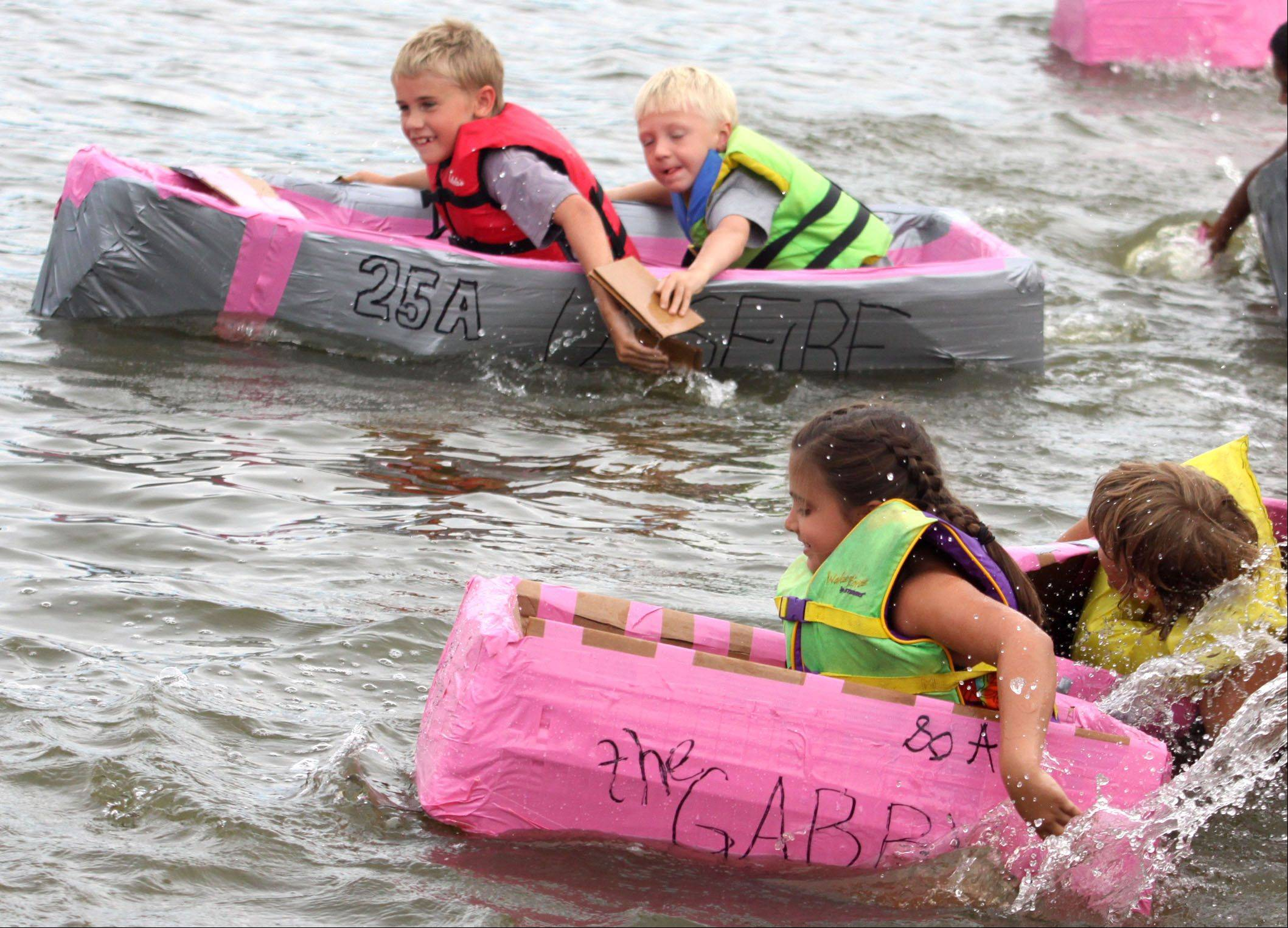 Racers navigate the Fox River during the Cardboard Boat Regatta juniors race as part of Founders' Days festivities in Algonquin Thursday night.