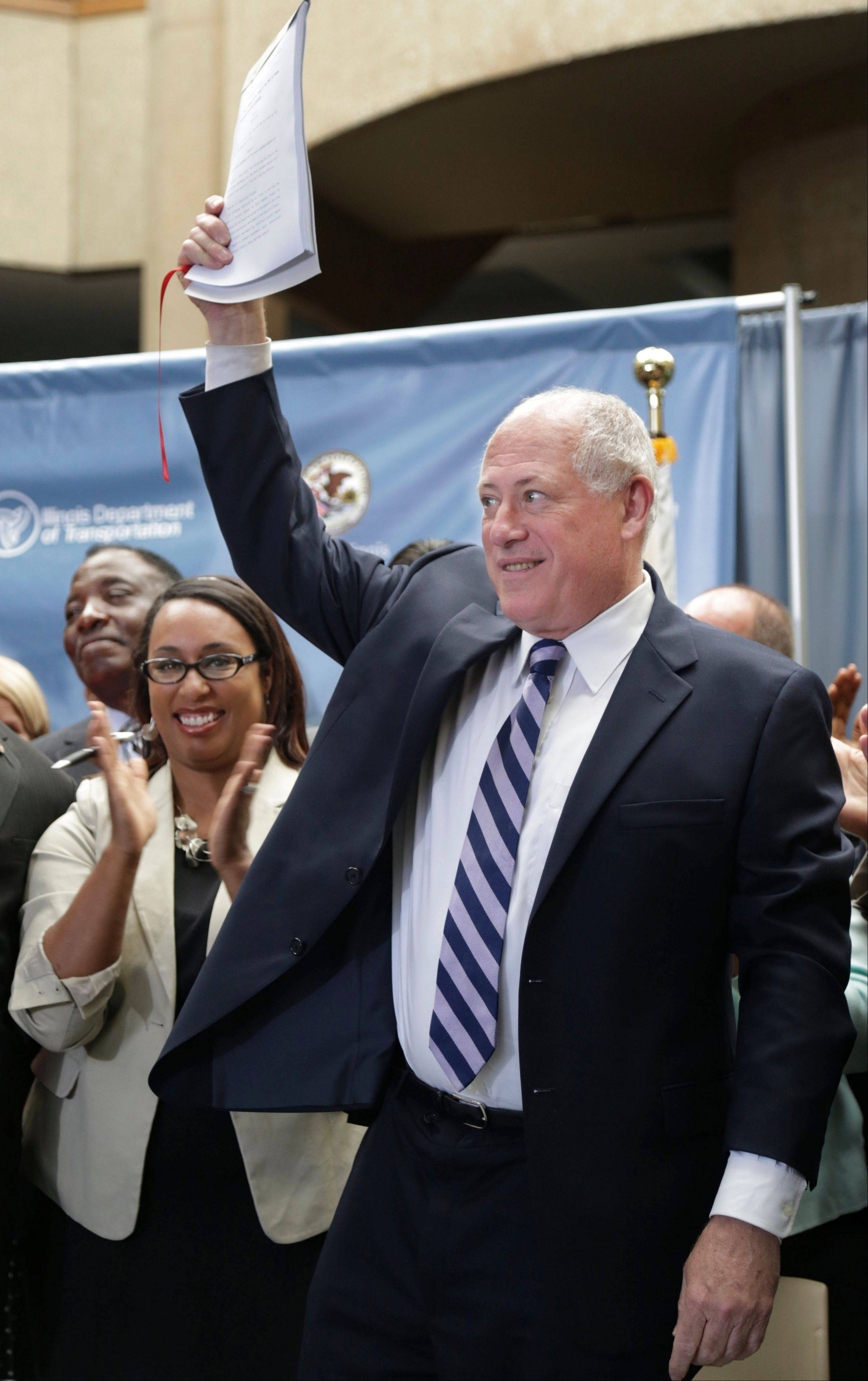 State Sen. Toi Hutchinson, left, celebrates after Gov. Pat Quinn signed a wide-ranging bill that will allow state officials to push forward on a third Chicago-area airport Thursday in University Park.
