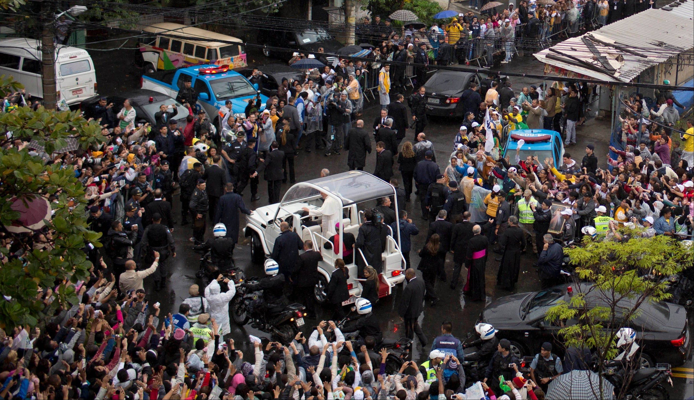 People line the street to greet Pope Francis as he arrives in his popemobile in the Varginha slum, part of the Manguinhos slum complex in Rio de Janeiro, Brazil, Thursday.