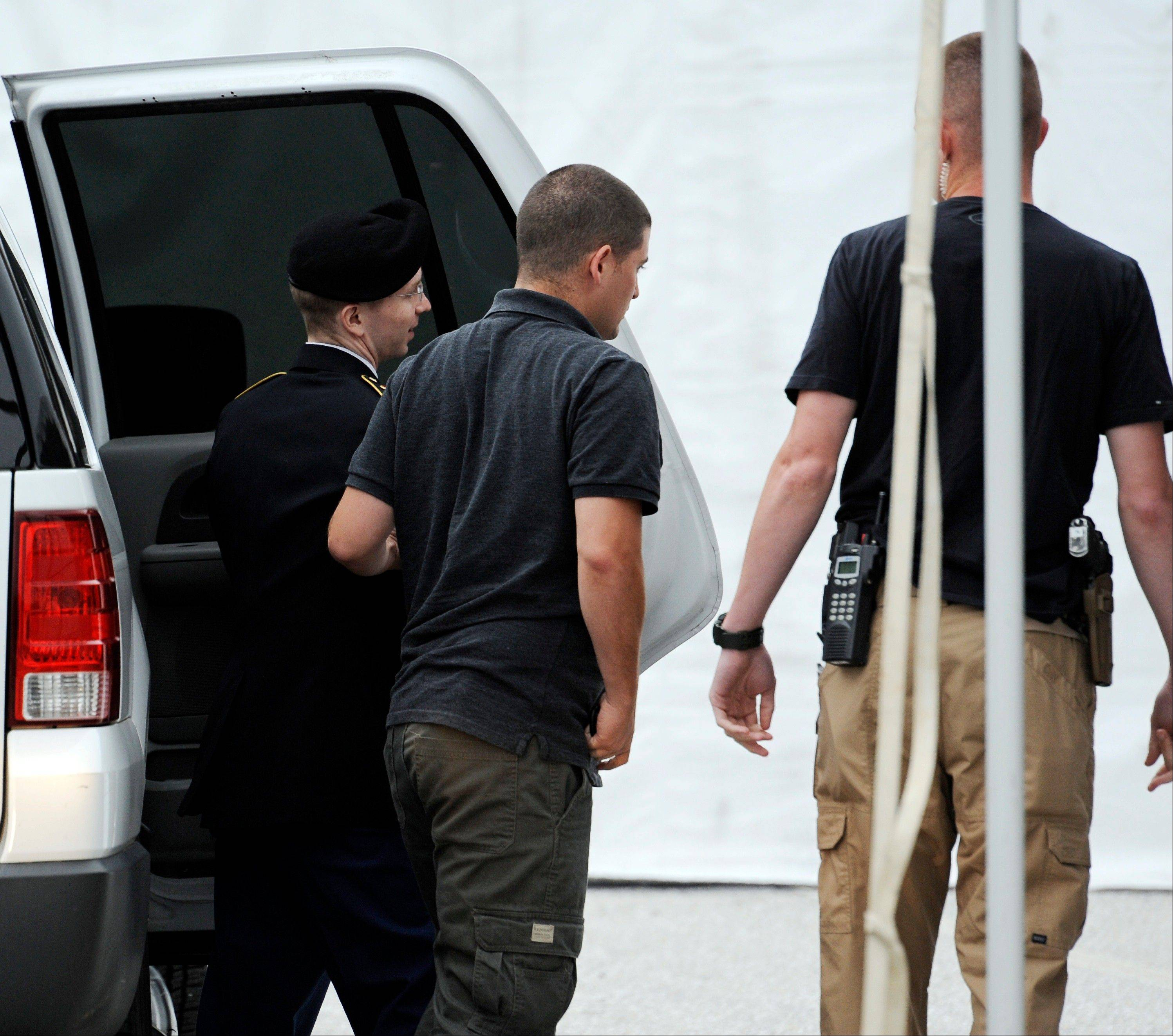 Army Pfc. Bradley Manning, left, is escorted into a courthouse for his court-martial at Fort Mead, Md., Thursday, July 25, 2013. Manning is charged with indirectly aiding the enemy by sending troves of classified material to WikiLeaks. He faces up to life in prison.