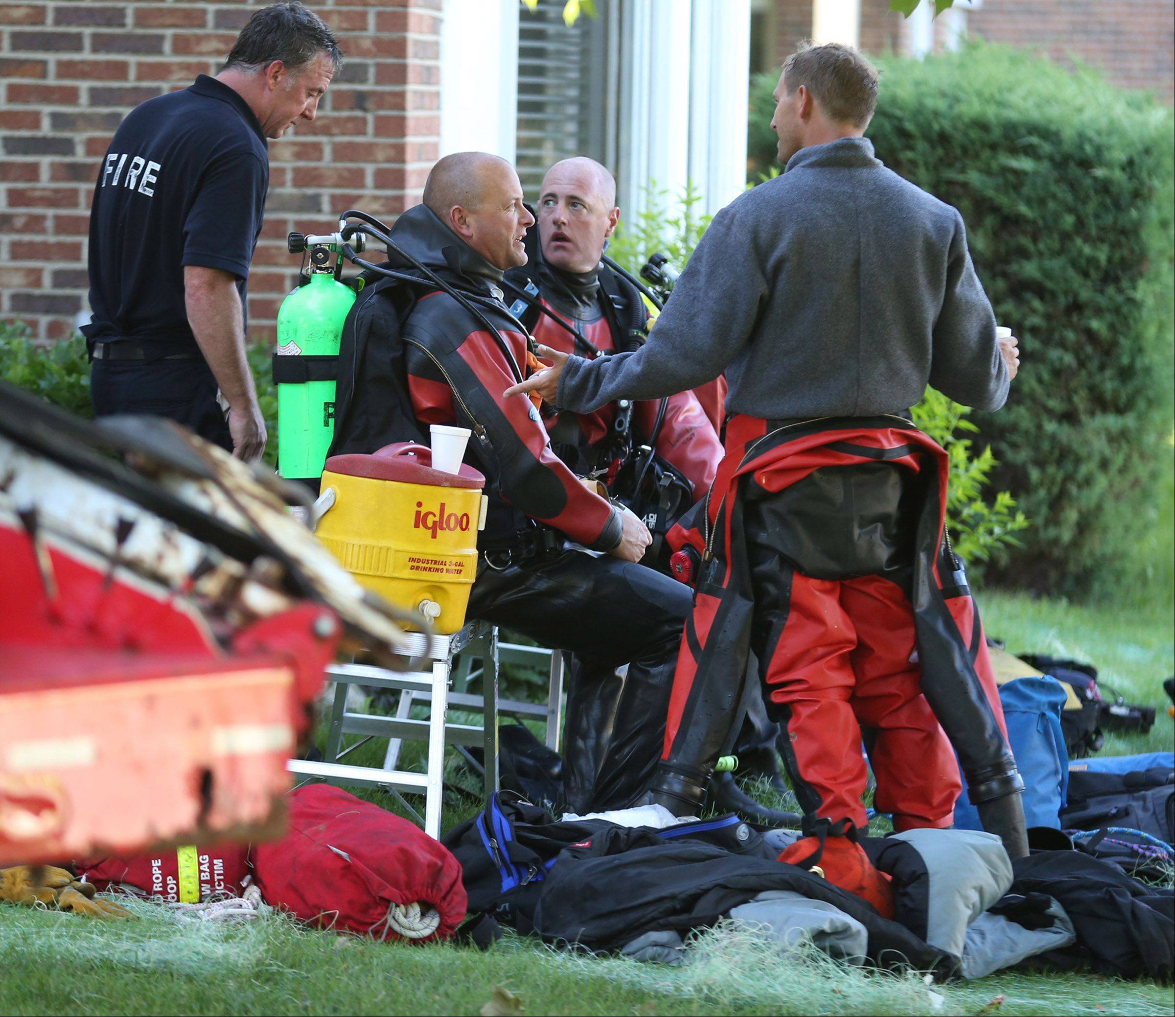 Rescue divers rest after pulling Henry Laseke from the SUV and putting him into an ambulance.