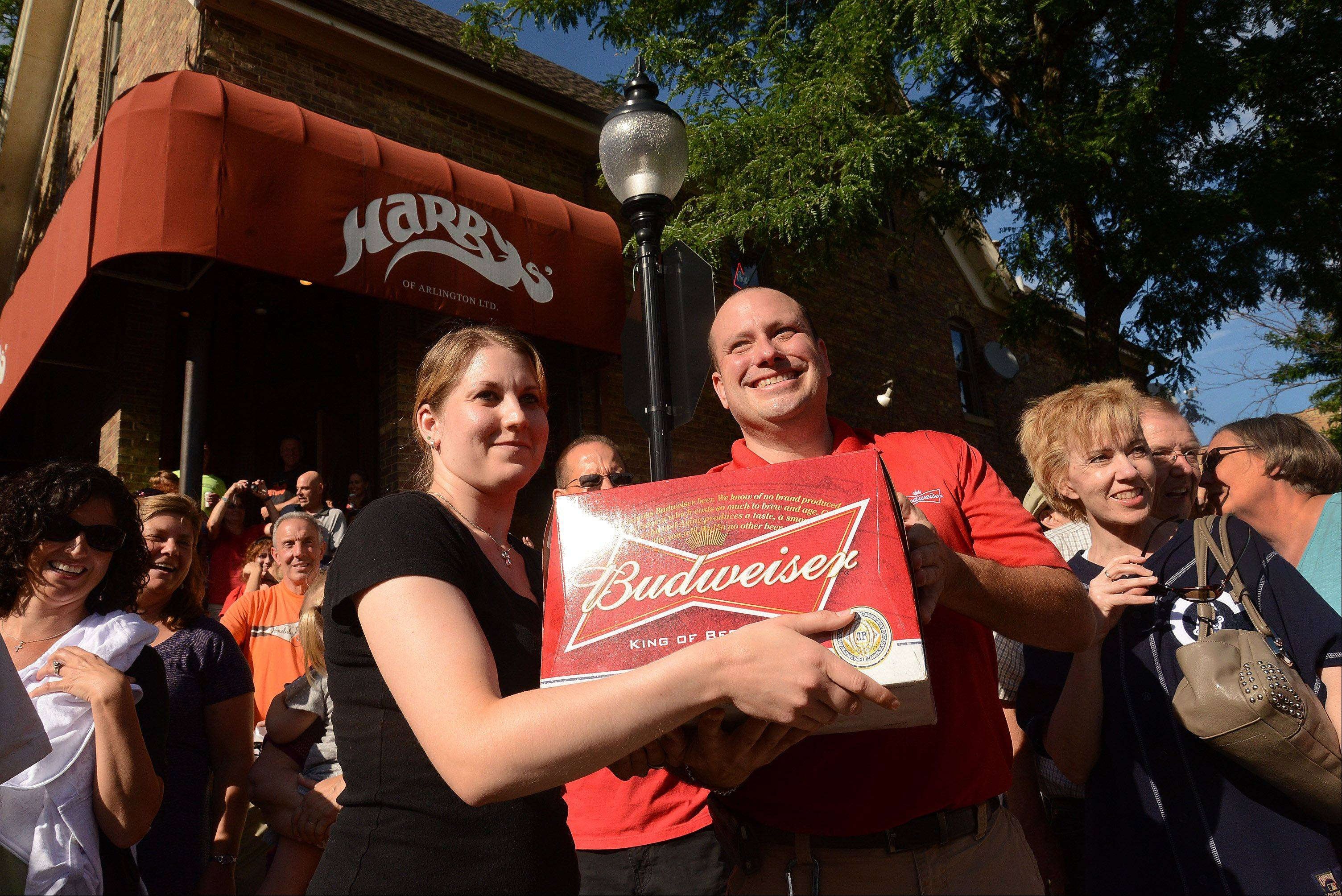 The Budweiser Clydesdales make a delivery to Harry's in downtown Arlington Heights. Jim Dvorak of Budweiser hands a case of Bud to waitress/bartender Tina Krentz.