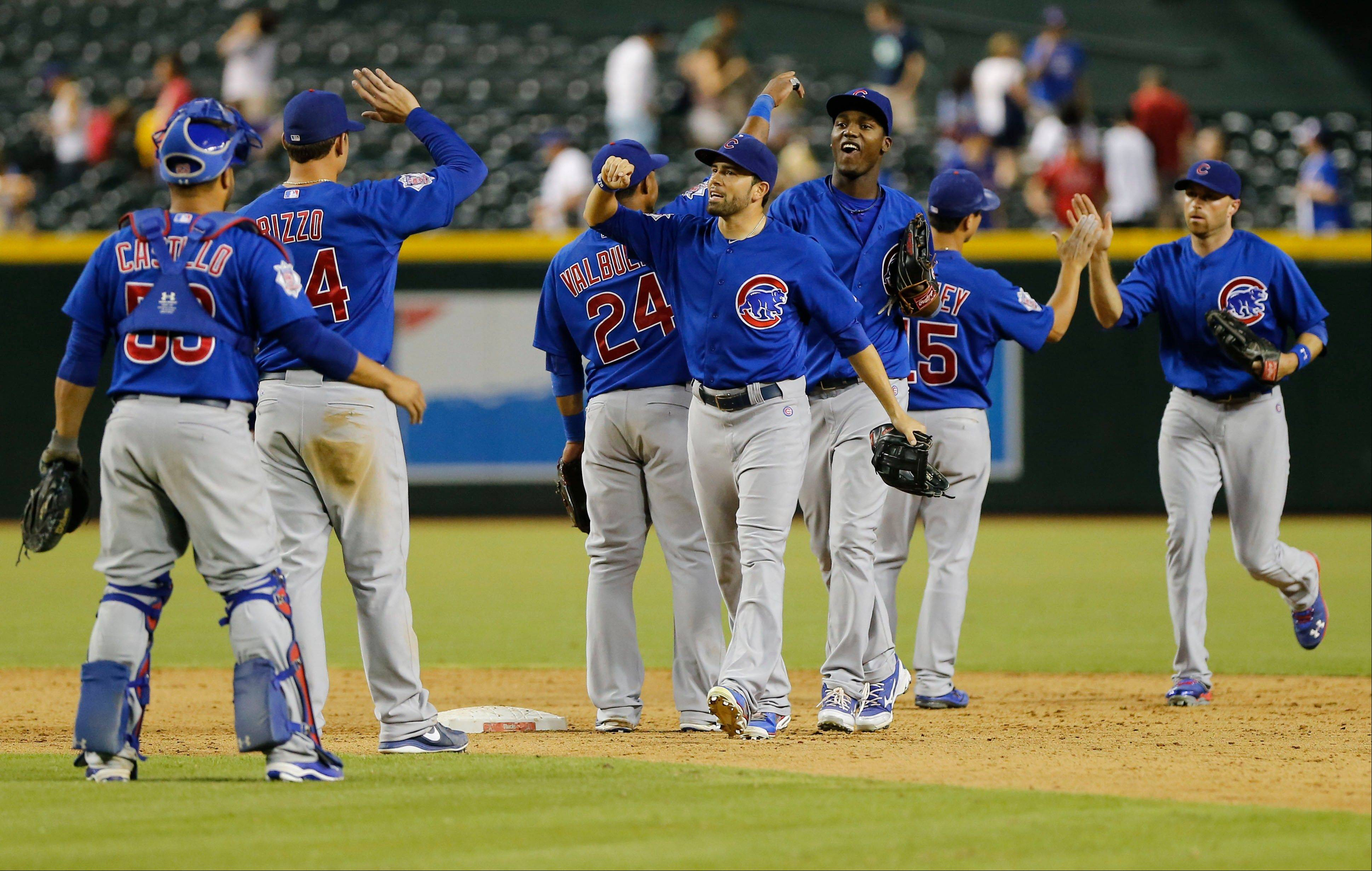 The Cubs celebrate their win against the Arizona Diamondbacks in Phoenix. The Cubs won 7-6 in 12 innings.