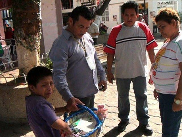In this image taken from video, Manuel Diaz Hernandez, a 10-year-old street vendor, weeps Monday as he is forced by a city inspector to throw away his goods that include candy and cigarettes, in Villahermosa, Mexico.