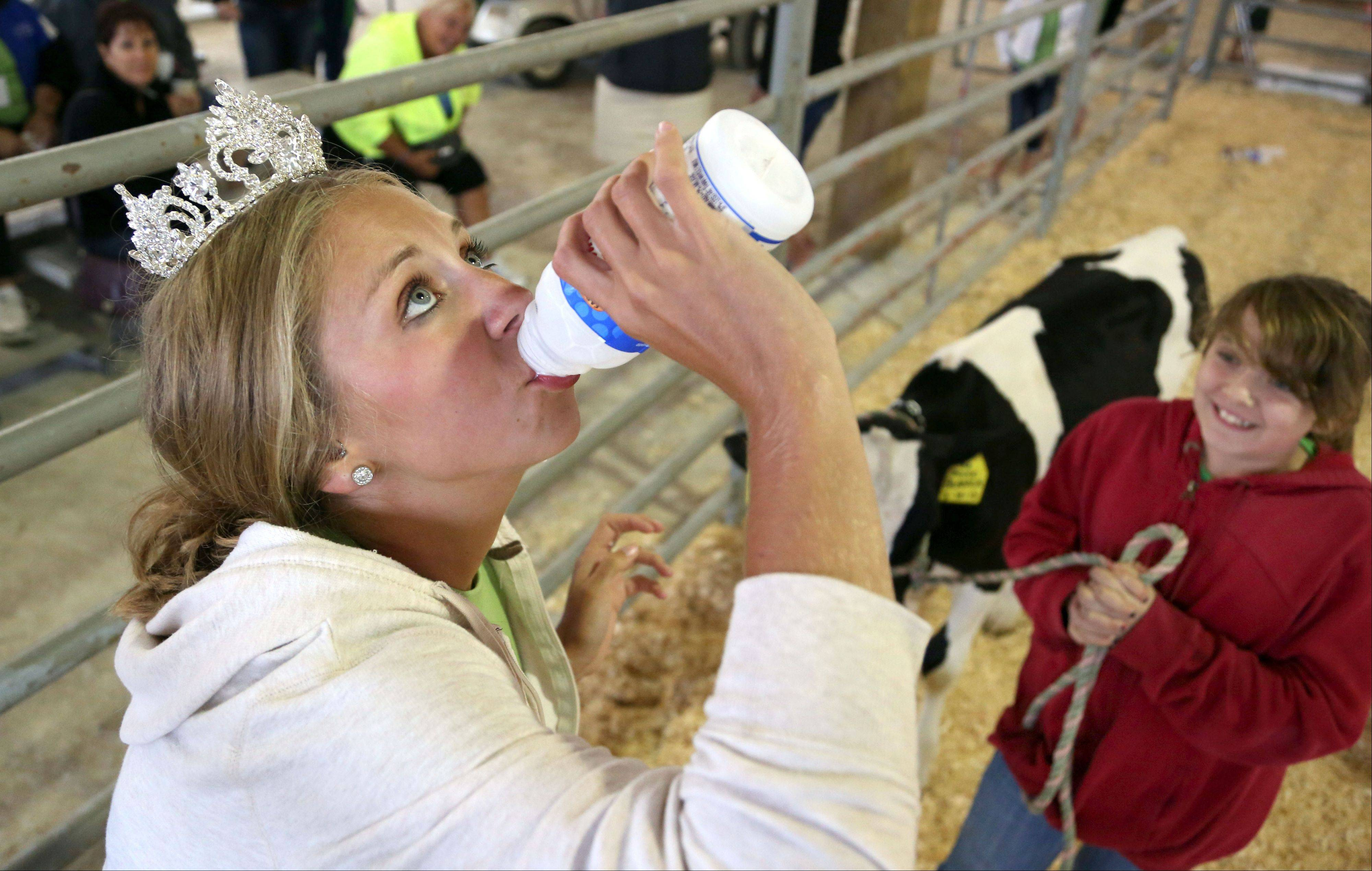 Miss Lake County Fair Queen Meghan Opolka, left, of Antioch, chugs milk as 11-year-old Sara Lincicome of Beach Park, looks on during Friday�s Crazy Cow Relay in the dairy barn at the Lake County Fair in Grayslake.