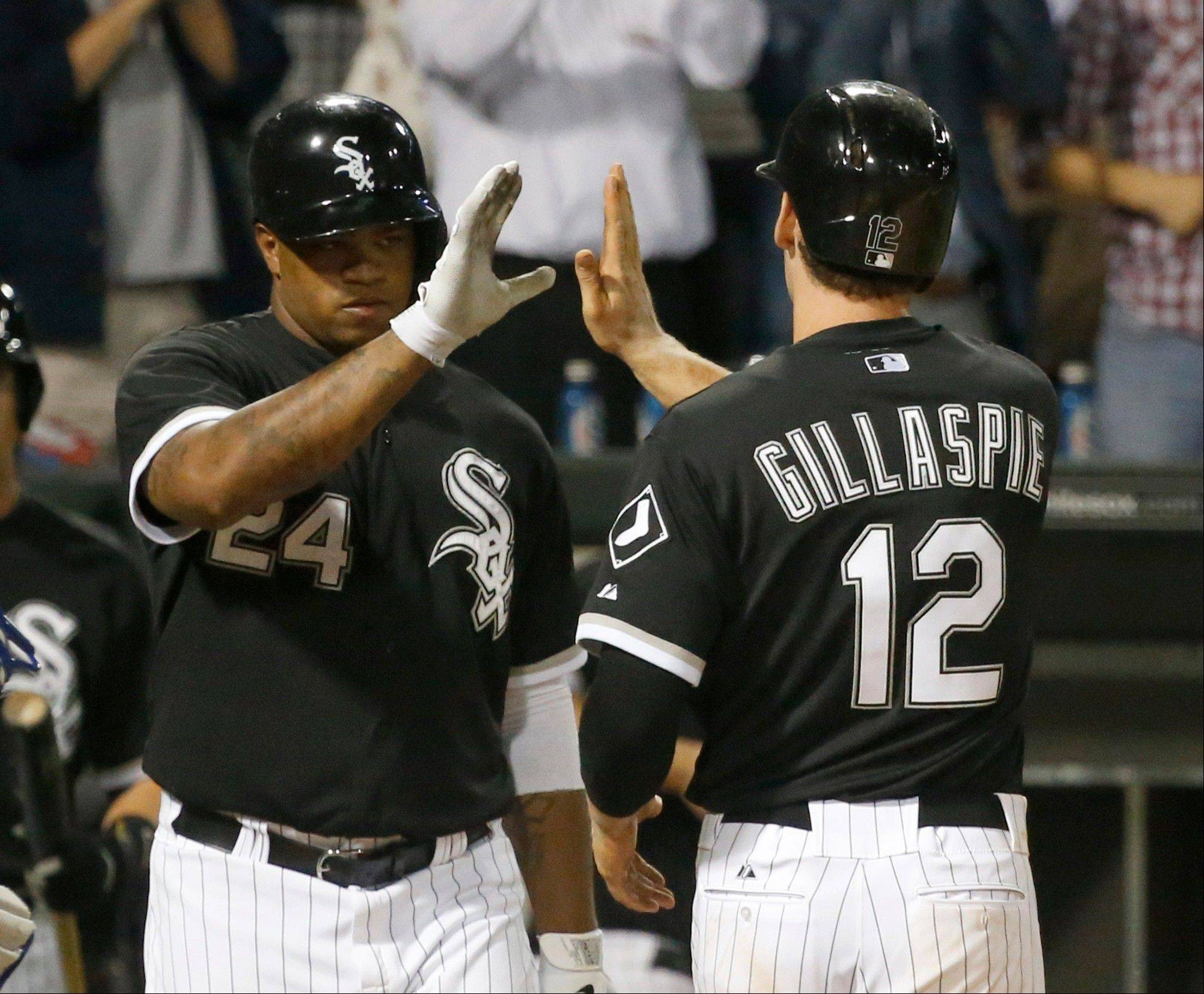 Chicago White Sox's Dayan Viciedo (24) greets teammate Conor Gillaspie outside the dugout after Gillaspie's home run off Kansas City Royals relief pitcher Kelvin Herrera during the eighth inning of a baseball game on Friday, July 26, 2013, in Chicago. (AP Photo/Charles Rex Arbogast)
