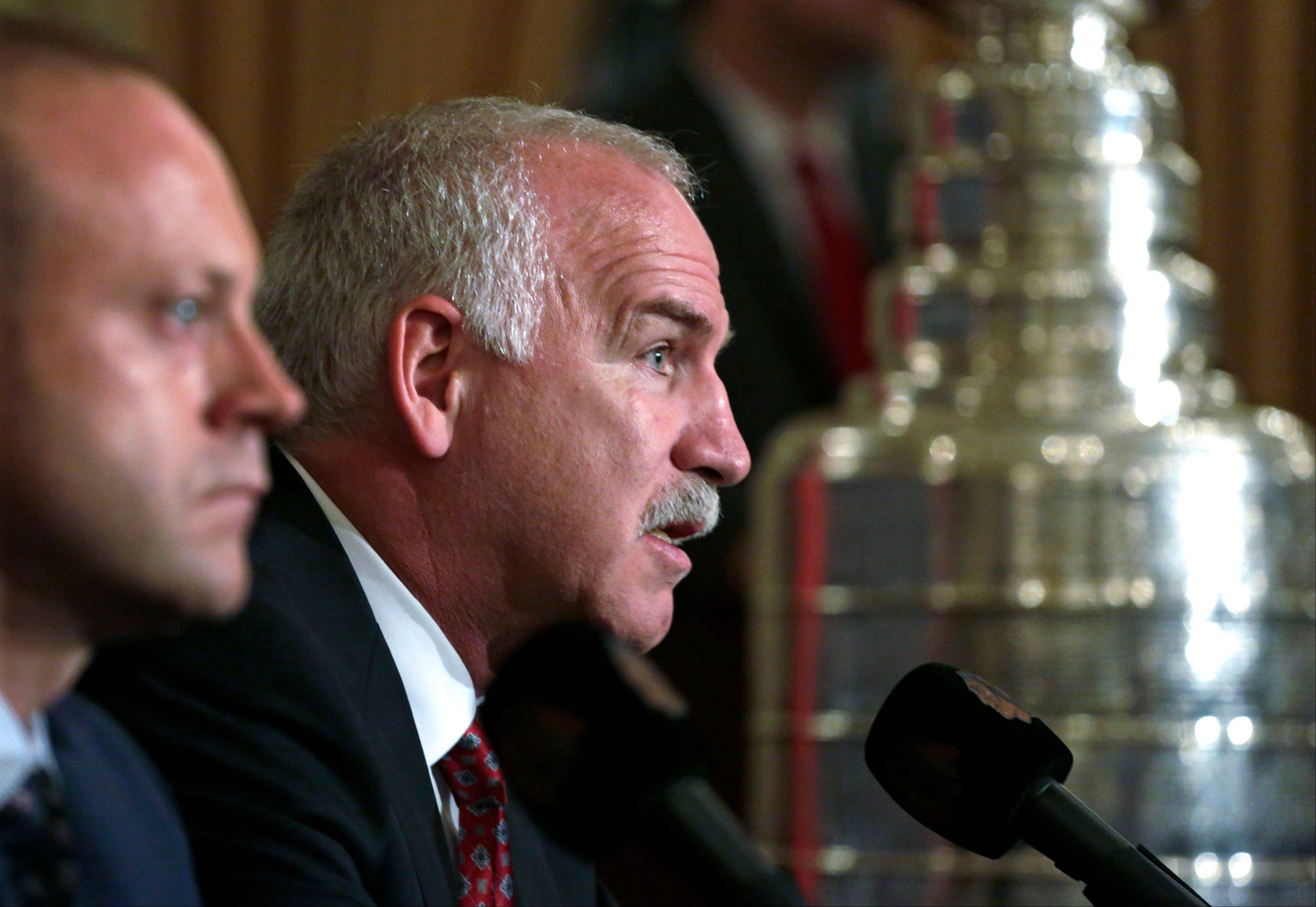 Blackhawks coach Joel Quenneville, right, talks about the three-year contract extention he received from general manager Stan Bowman, left.