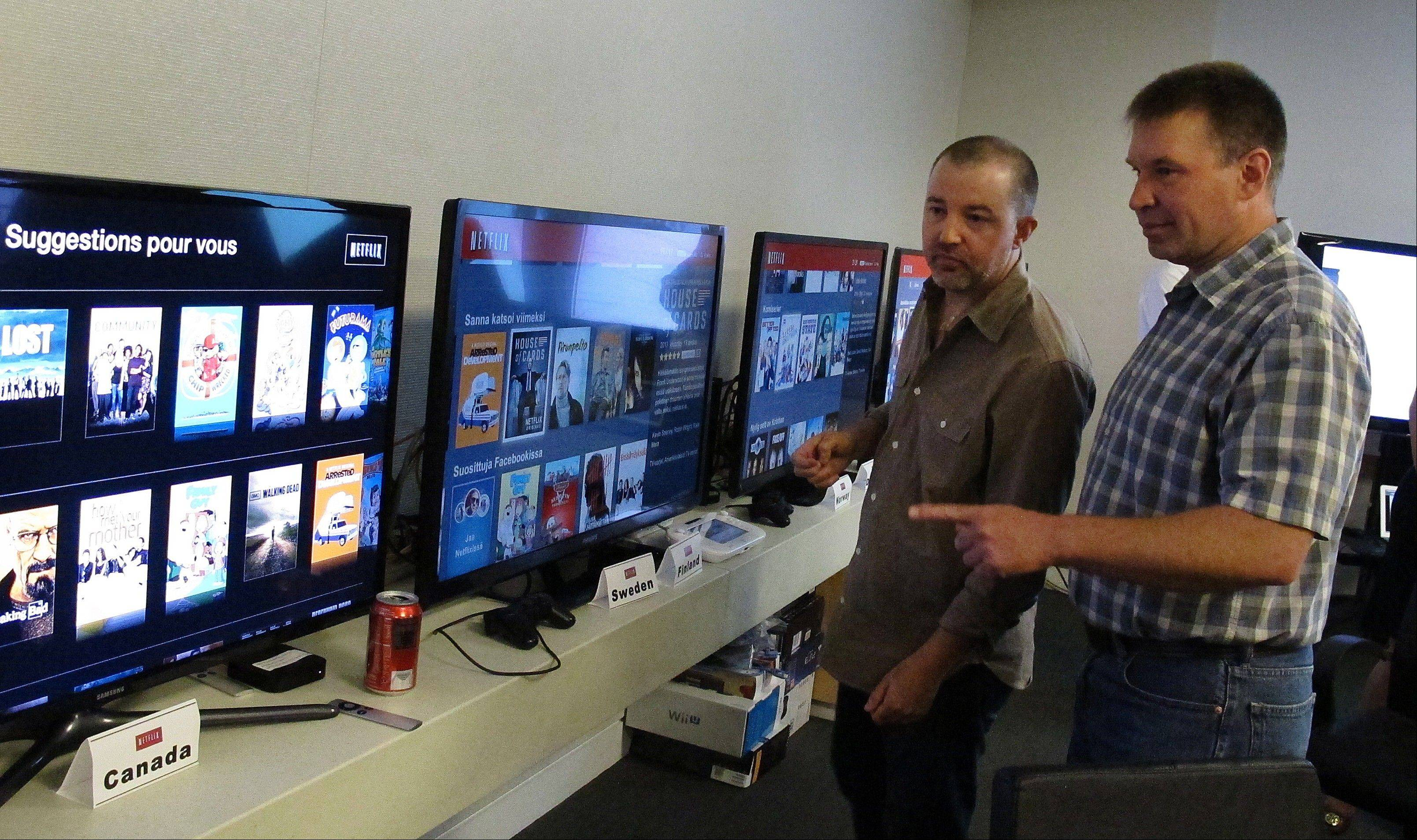 "Chris Jaffe, Netflix VP of Product Innovation, left, and Bob Heldt, Director of Engineering, look over video displays as they await the debut of ""Orange is the new black"" in Los Gatos, Calif."