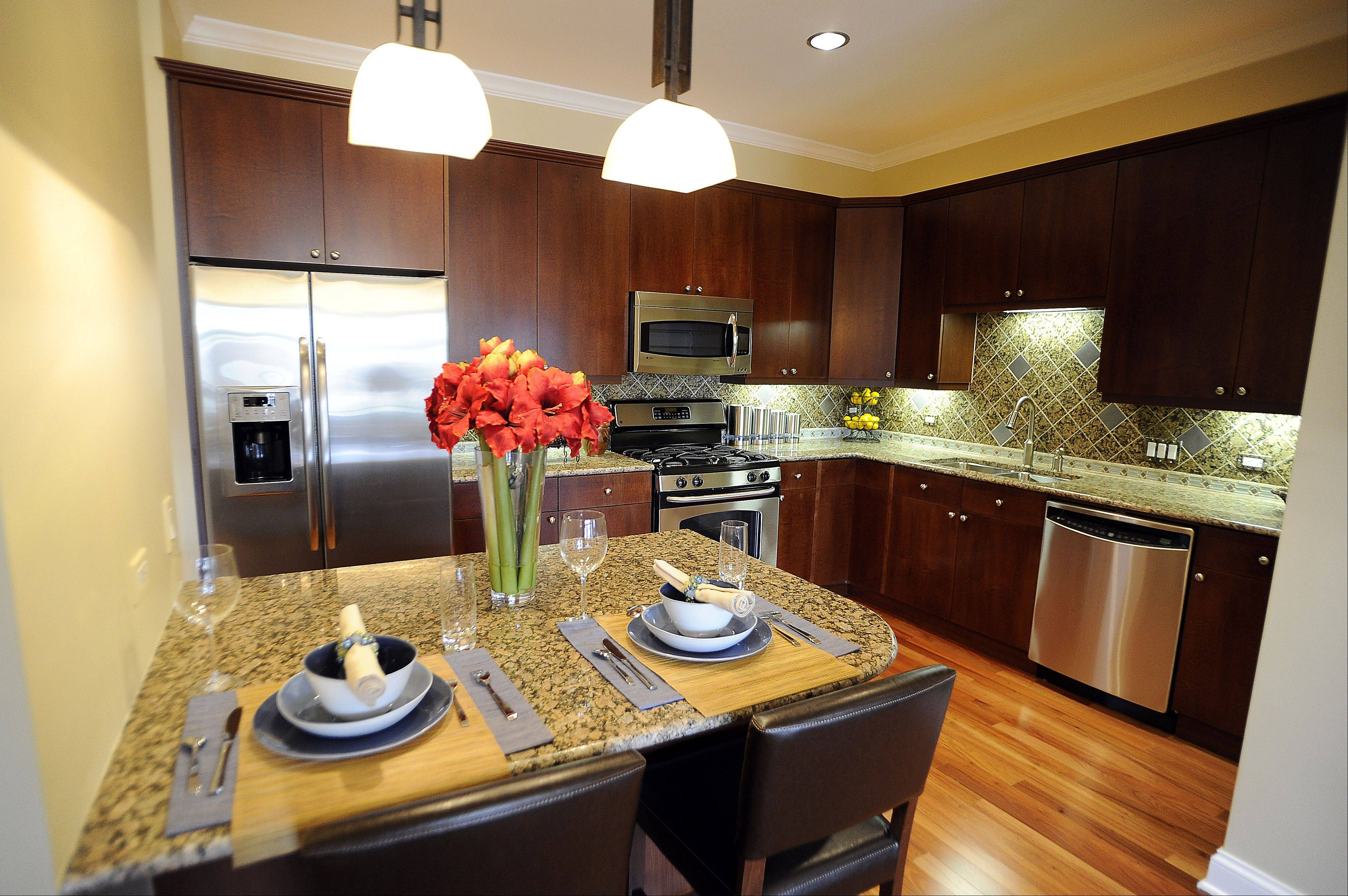 Cherry wood kitchen cabinets are shown in Prairie Park's Waterford model.